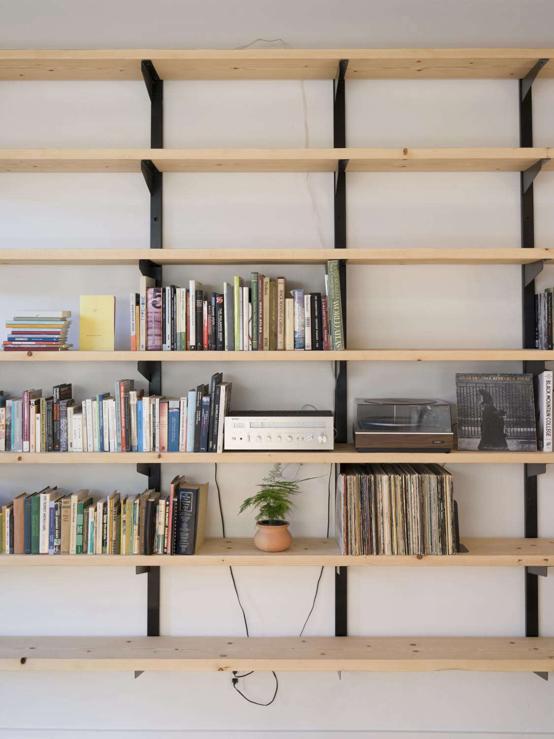 A sharing library of books and records sits on shelves of locally milled fir with brackets by Phloem Studio.