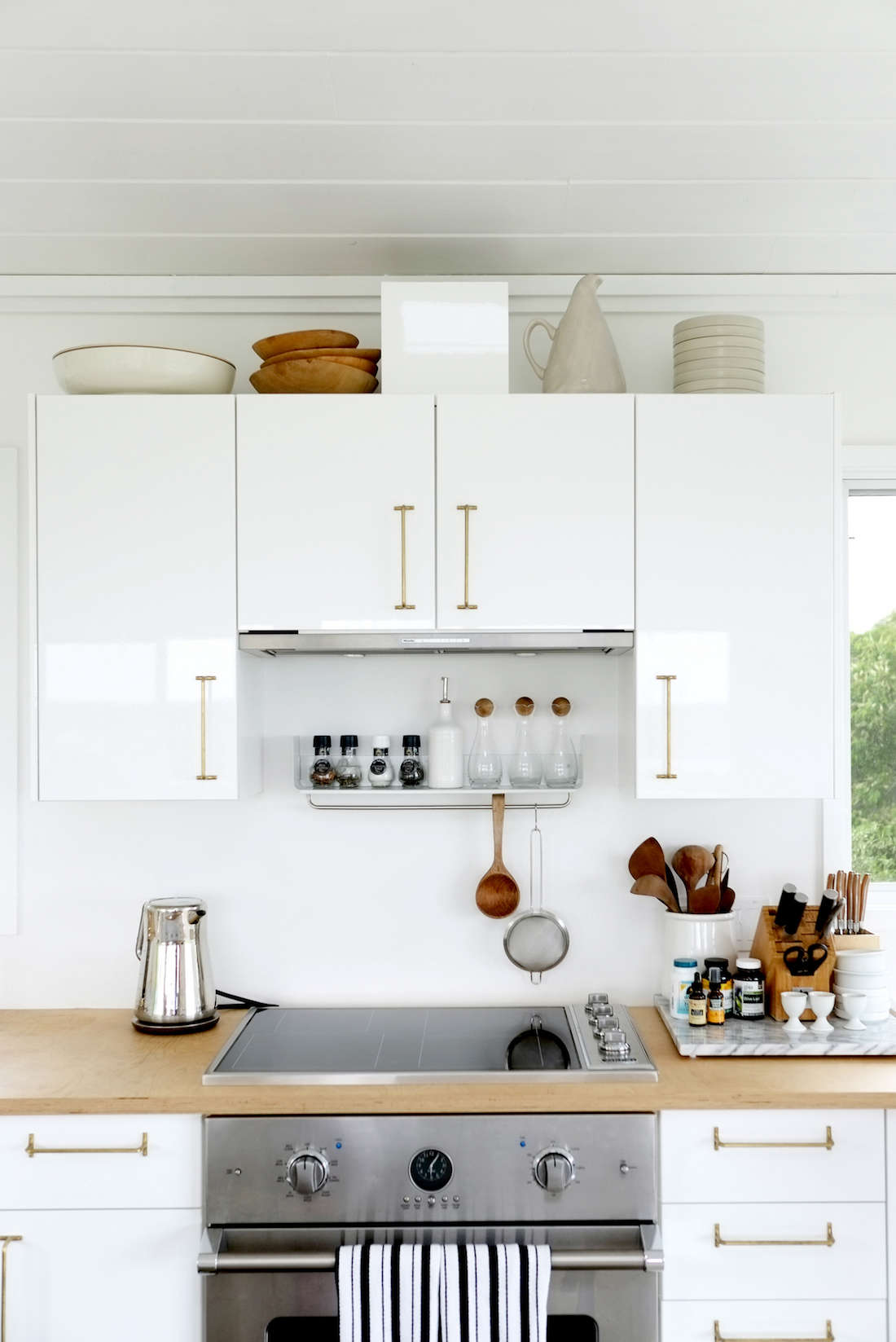 The kitchen cabinets are high-gloss Ringhult fromIkea, and thecabinet pulls are Japanese Futagami Brass Towel Bars. The Miele vent hood is concealedbehind a cabinet, and its exhaust duct is hidden behind a custom cabinet detail on top.