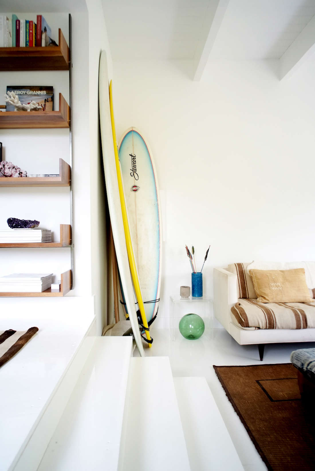 Family surfboards are stashed in the corners of the sunroom. Floors arehigh-quality plywood with a glossy white epoxy finish—the idea of client Dylan Dodd, who Greenberg says &#8