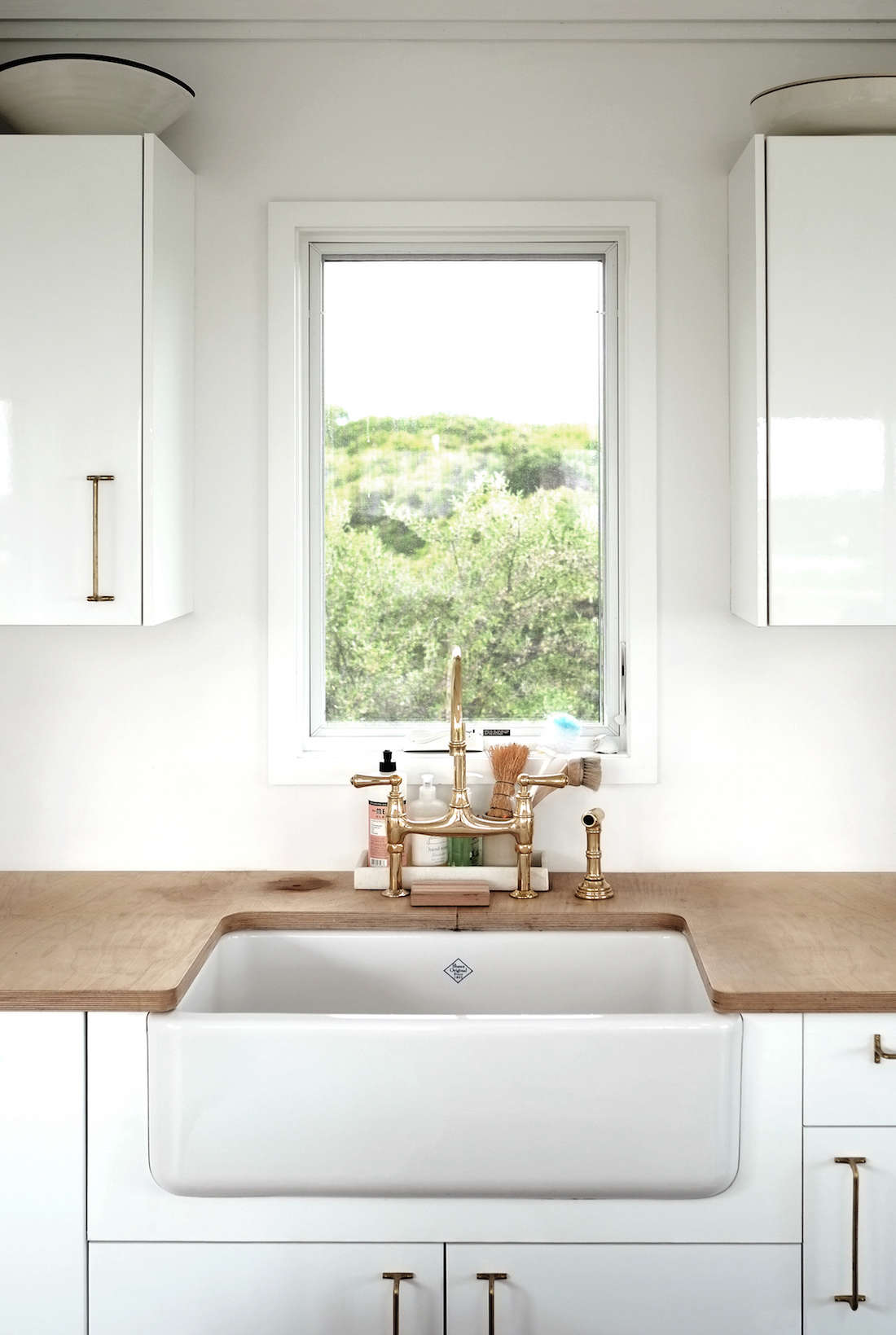 The kitchen countertops are marine-grade Baltic birch plywood, which were intended as a placeholderbut eventually won over the owners. The brass kitchen faucet and apron sink are both from Rohl. A single kitchen window frames a view of the surrounding spruce and sumac trees.