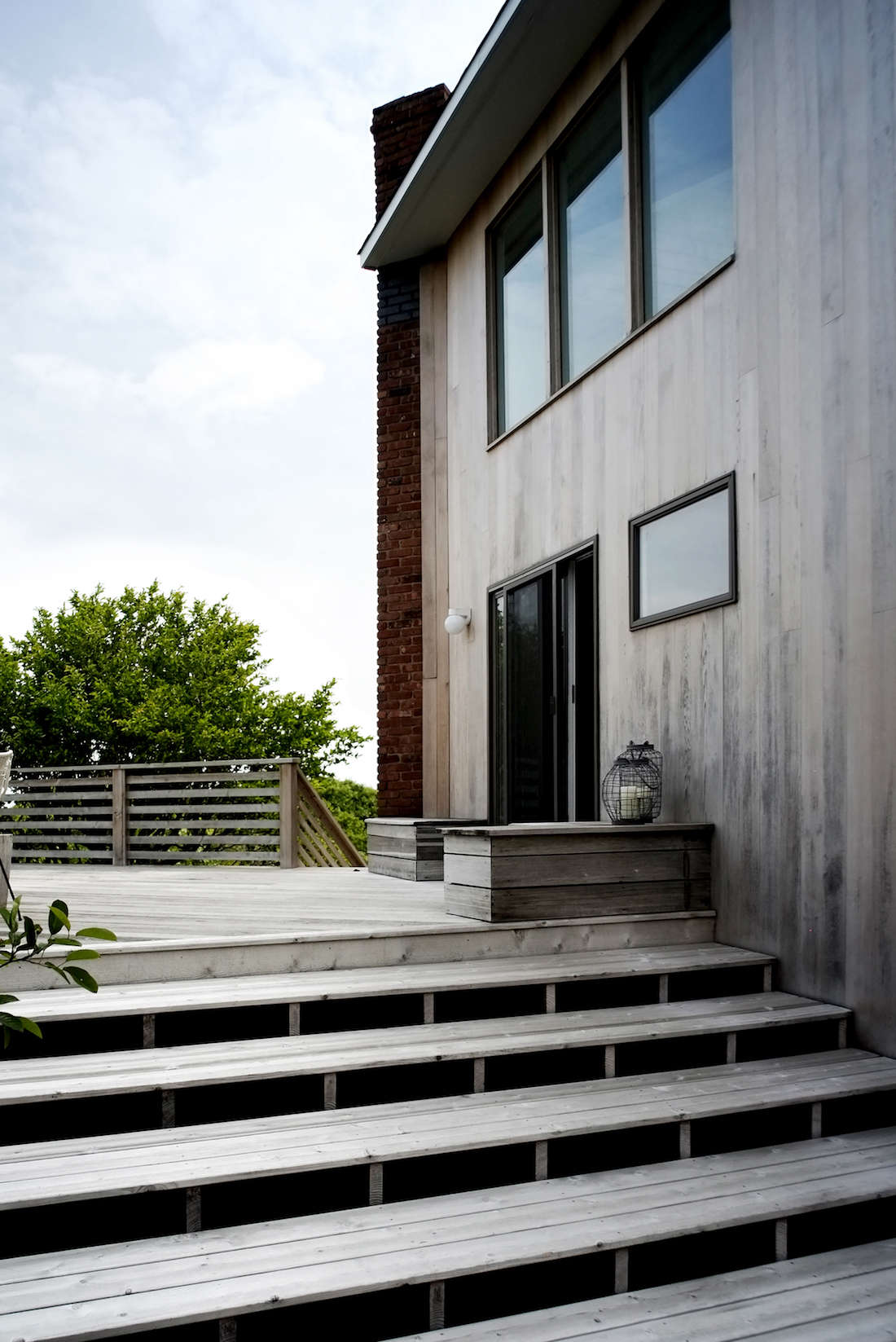 The existing cedar siding and outdoor lighting was original to the house, which sits atop a densely wooded bluff at the end of a rugged dirt road in Montauk.
