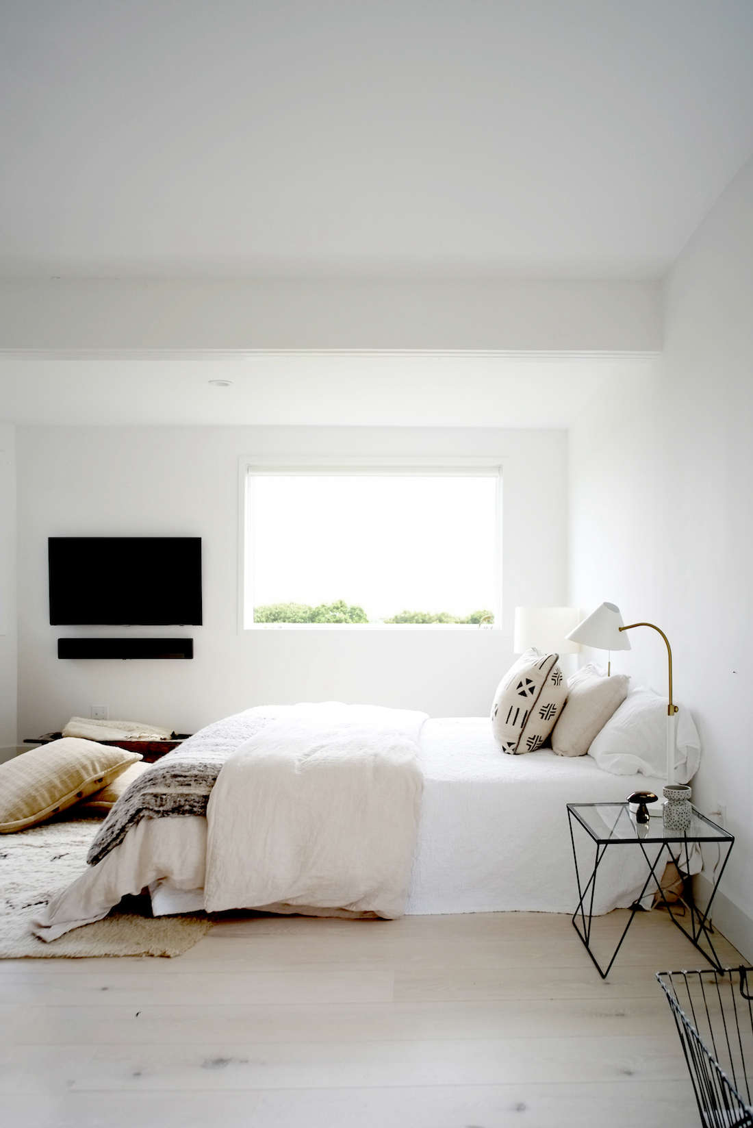 The master bedroom makes use of textiles sourced by the owners from all over the world. The Sony television and sound bar are so cleanly mounted that they manage to fit with the surroundings.
