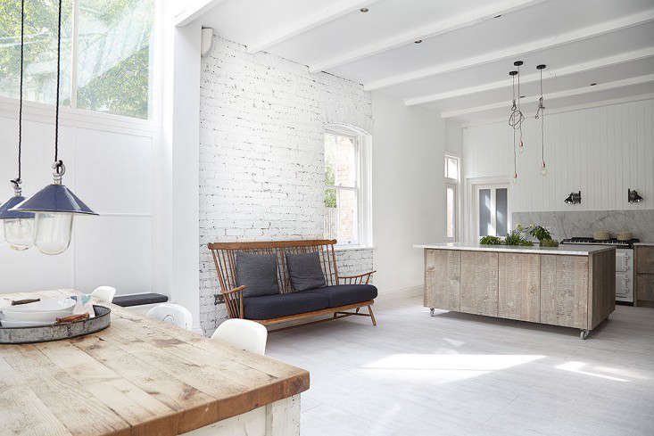 the open kitchen is fronted by a marble topped island built from wood textured  10