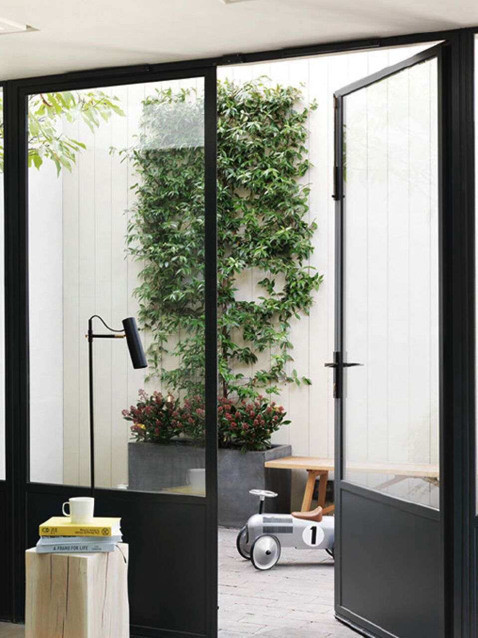 A Notting Hill Townhouse Tailored for Living by Charles Mellersh Steel framed glass doors open to a courtyard in a remodeled historic Notting Hill townhouse, interior design by Charles Mellersh   Remodelista