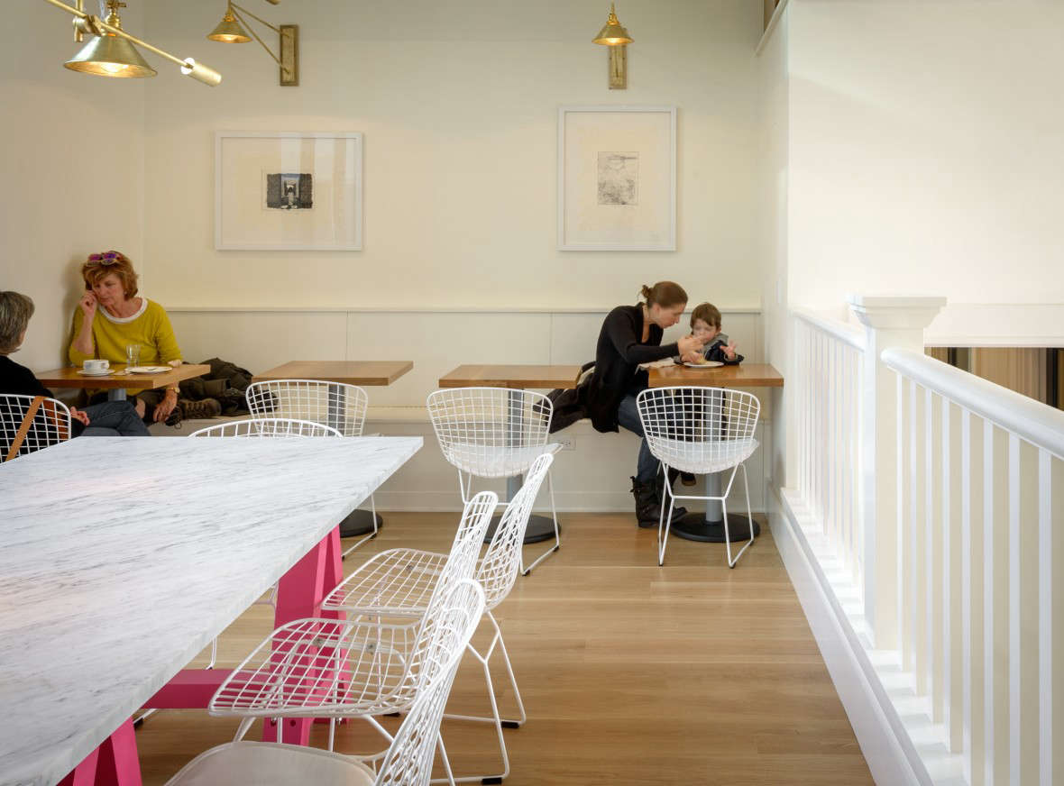 On the mezzanine level: additional cafe seating and a communal marble table with pink-painted trestles.