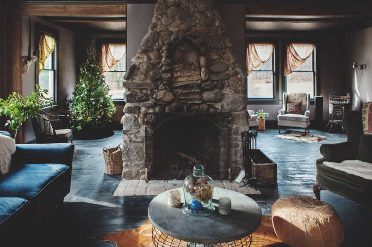 Bohemian Mastermix Foxfire Mountain House in the Catskills The floor to ceiling rustic stone fireplace in the lounge area was uncovered beneath a layer of drywall. Both the ceilings and floors received a new coat of black paint.