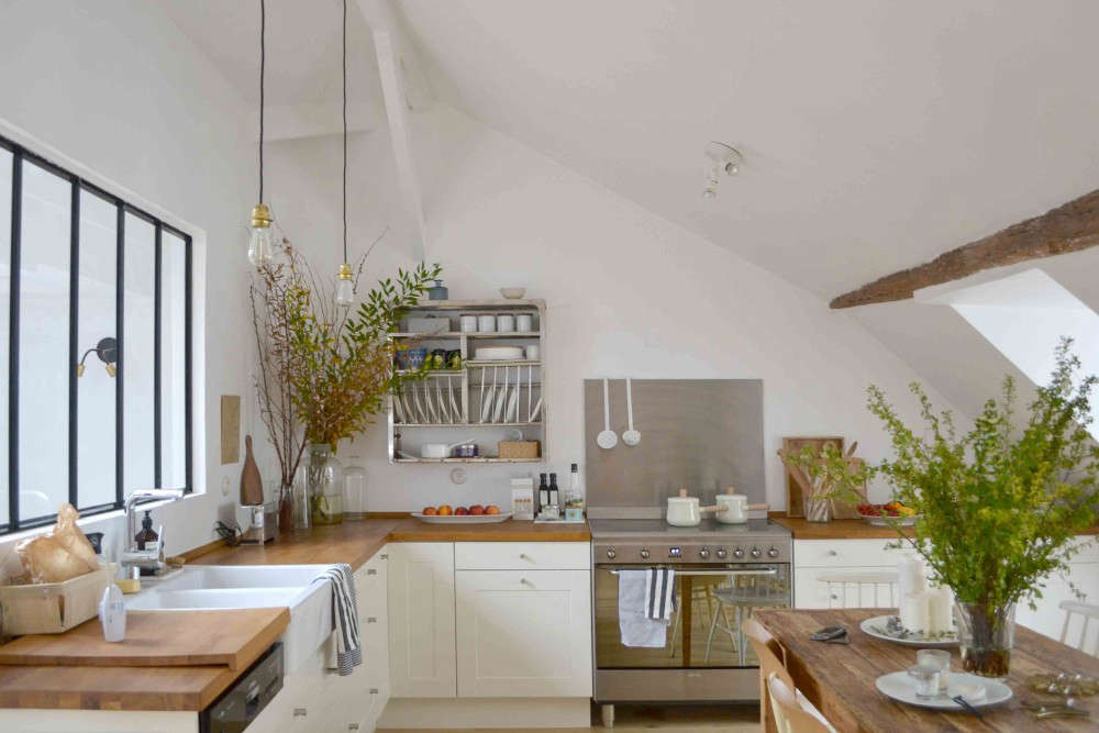 The couple installed an Ikea Grytnäs kitchen—counters, cabinets, and a sink—and personalized it. A stainless steel plate rack and Smeg gas range with a stainless backsplash add an industrial element to the warm space. Lucille made the pendant lamps herself.