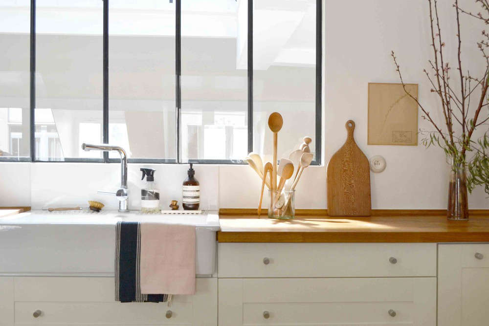 The Ikea sink and birch countertop are fronted by a large window. The counter soaps are from Aesop.