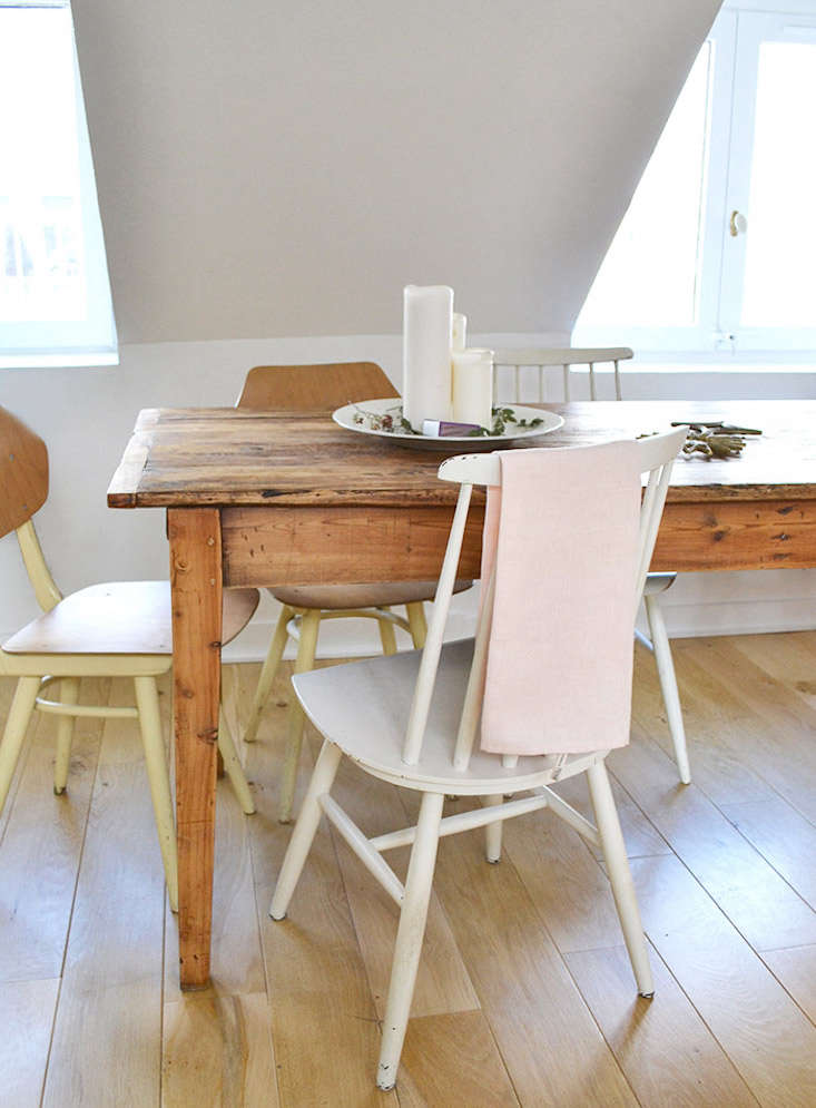 An old harvest table is paired with vintage white Fanett Dining Chairs by Finnish architect Ilmari Tapiovaara.