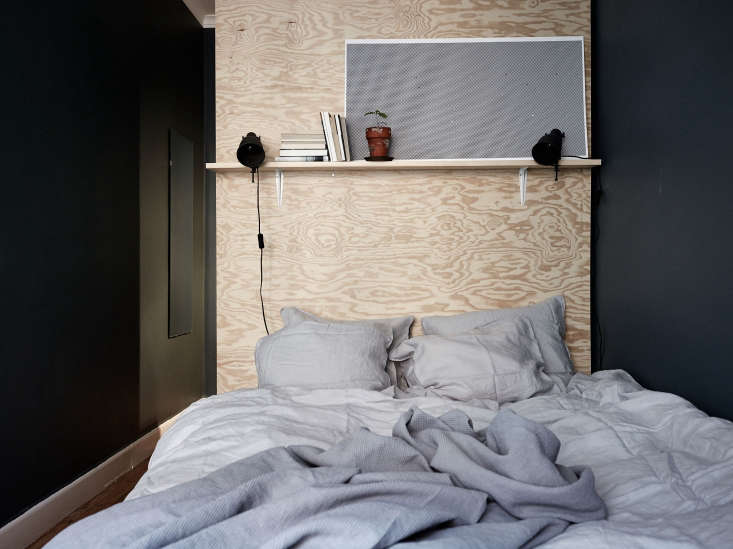 A plywood shelf above the bed atA Summery Flat in Stockholm, with Affordable Small-Space Ideas to Steal.