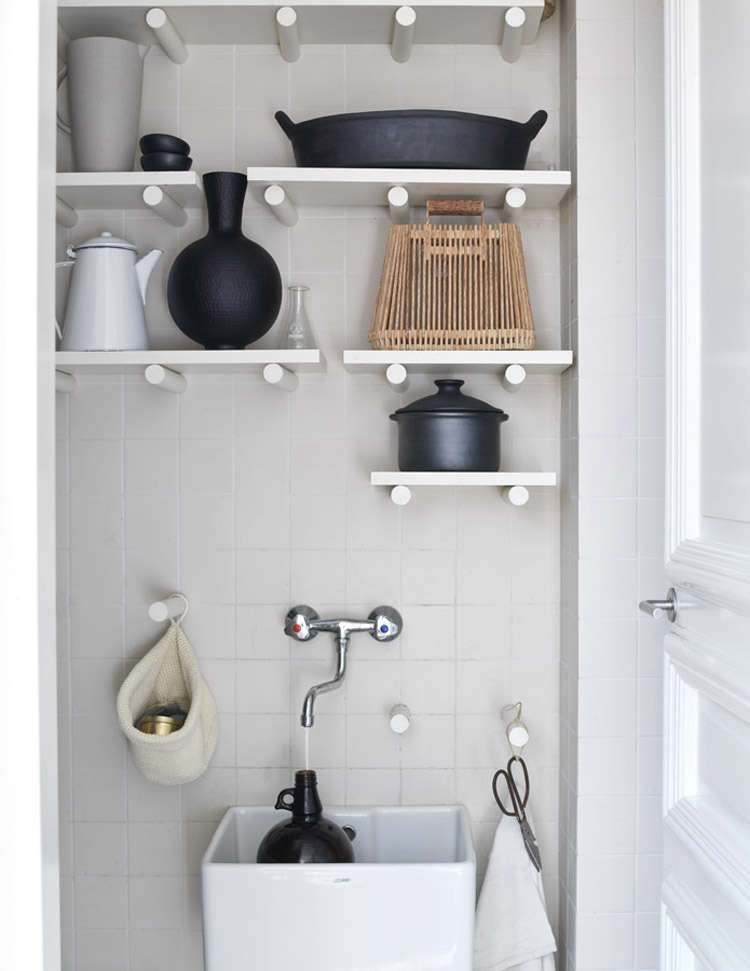 In a small but smart utility closet, white dowels serve as both pegs and brackets for shelves. See Steal This Look: The Organized Utility Closet, Complete with Sink.