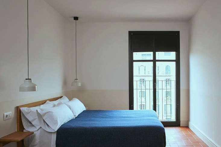 a simple guest bedroom with two toned walls and original tiledflooring. the h 16