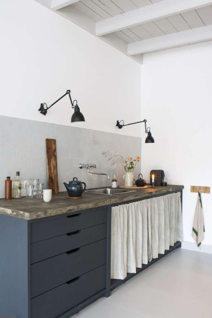 Applying a curtain to her kitchenette, Dutch designer Christien Starkenburg made a studio kitchen with a sink, backsplash, and a few drawers.