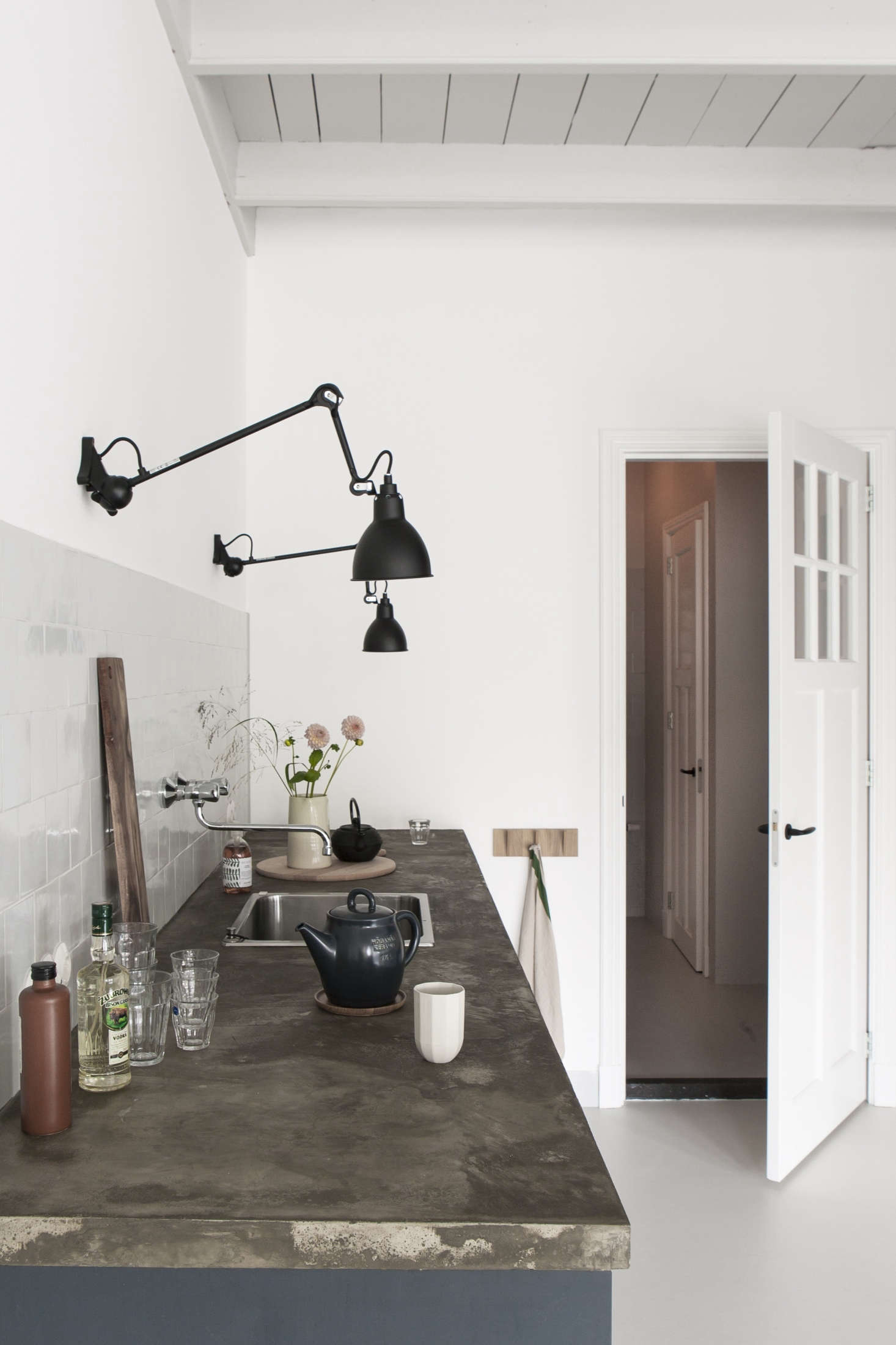 The adjustable sconces are French classics by Lampe Gras.