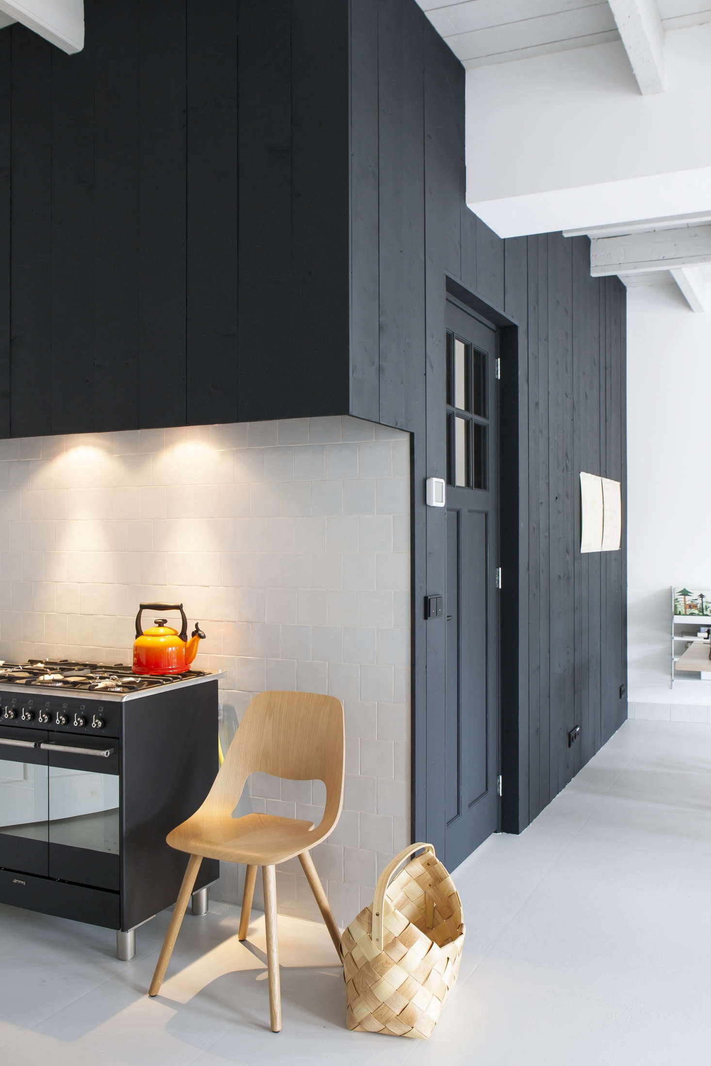 Black-stained pine paneling matches the kitchen millwork. A Vitra chair stands next to a Smeg range. The fridge (not shown) is set in a cabinet near the stove.