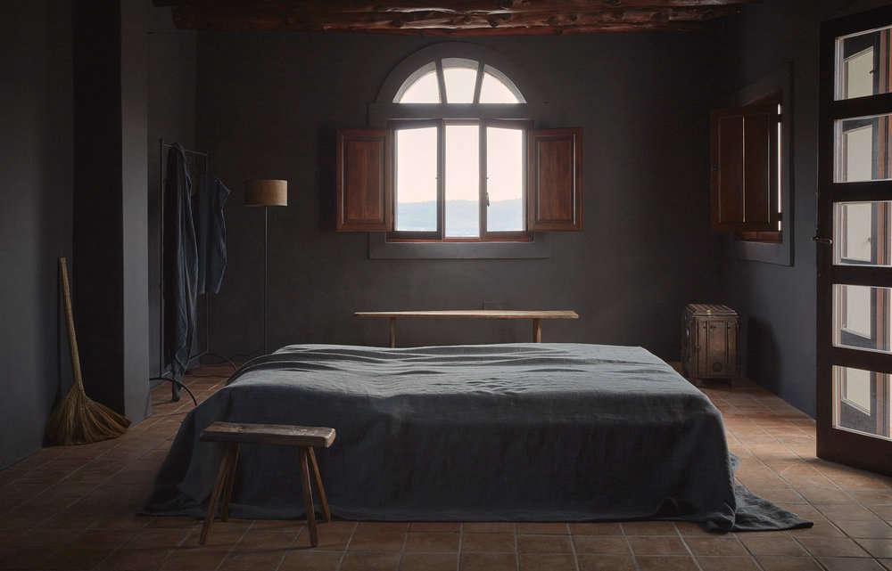 Gray bedroom with linen bedding steel-framed windows at La Granja Ibiza, a Design Hotels retreat on a 16th century finca | Remodelista