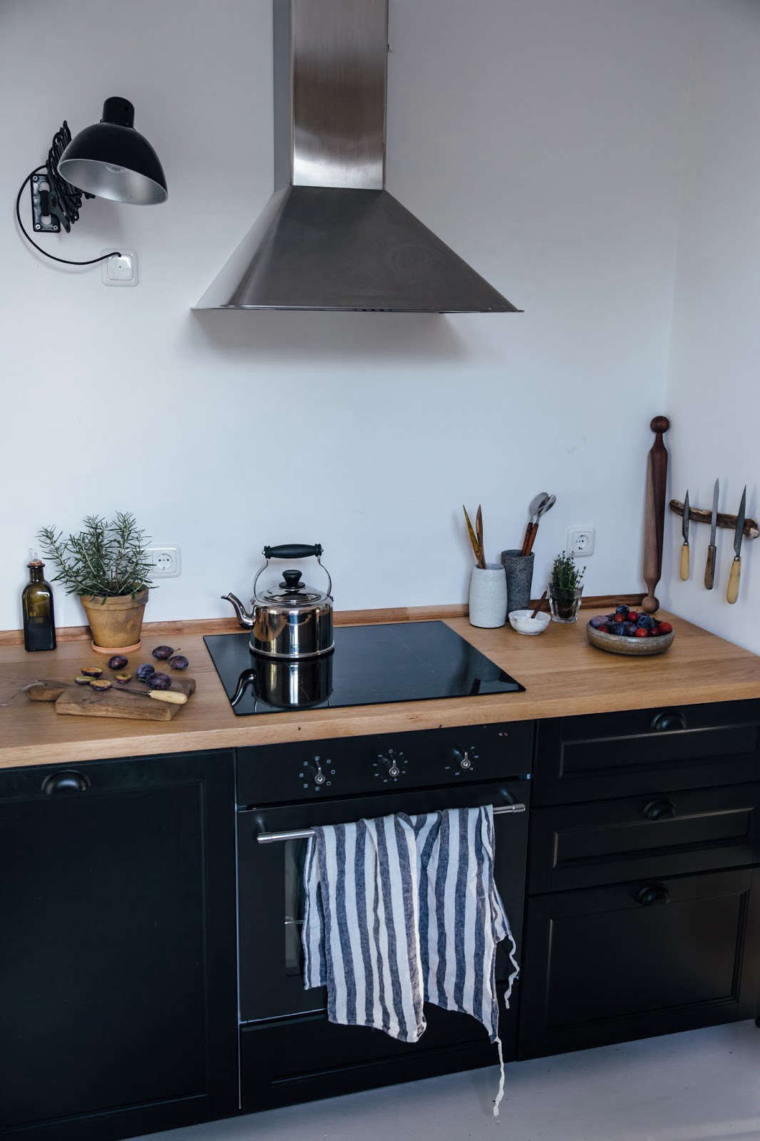 An Ikea range with induction cooktop (see the Nutid). Laura and Nora personalized the design with their own accessories, including a rustic knife rack and scissor lights that they found on eBay (for a similar design, consider the Scissor Arm Pharmacy Wall Light and see more options here).