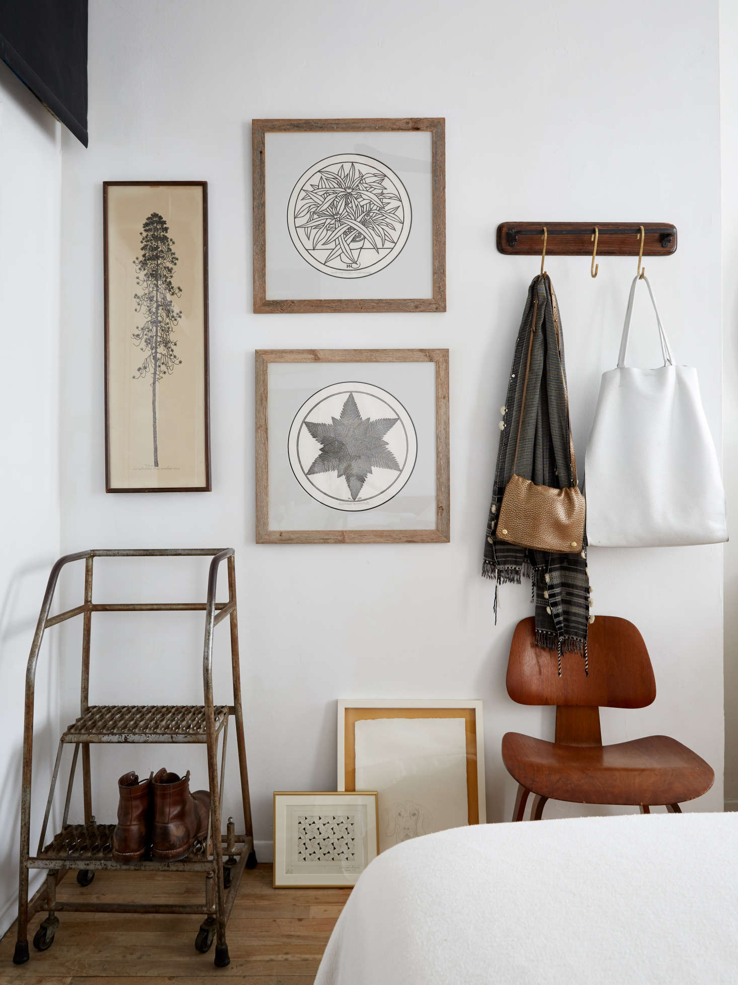 Framed black and white prints and an industrial step stool on wheels in an artful apartment bedroom