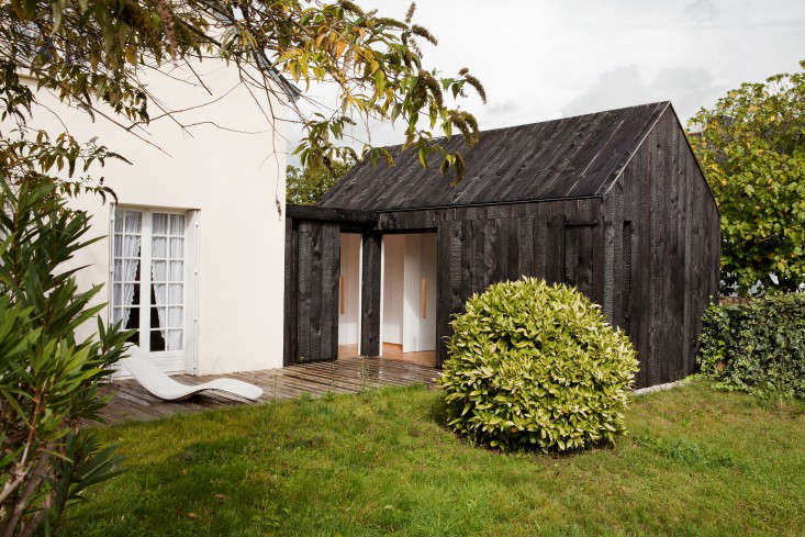 A charred wood cottage attached to a bright white house on the coast of Brittany by NeM Architects from Before and After: A Charred Wood Cottage, on a $45K Budget.