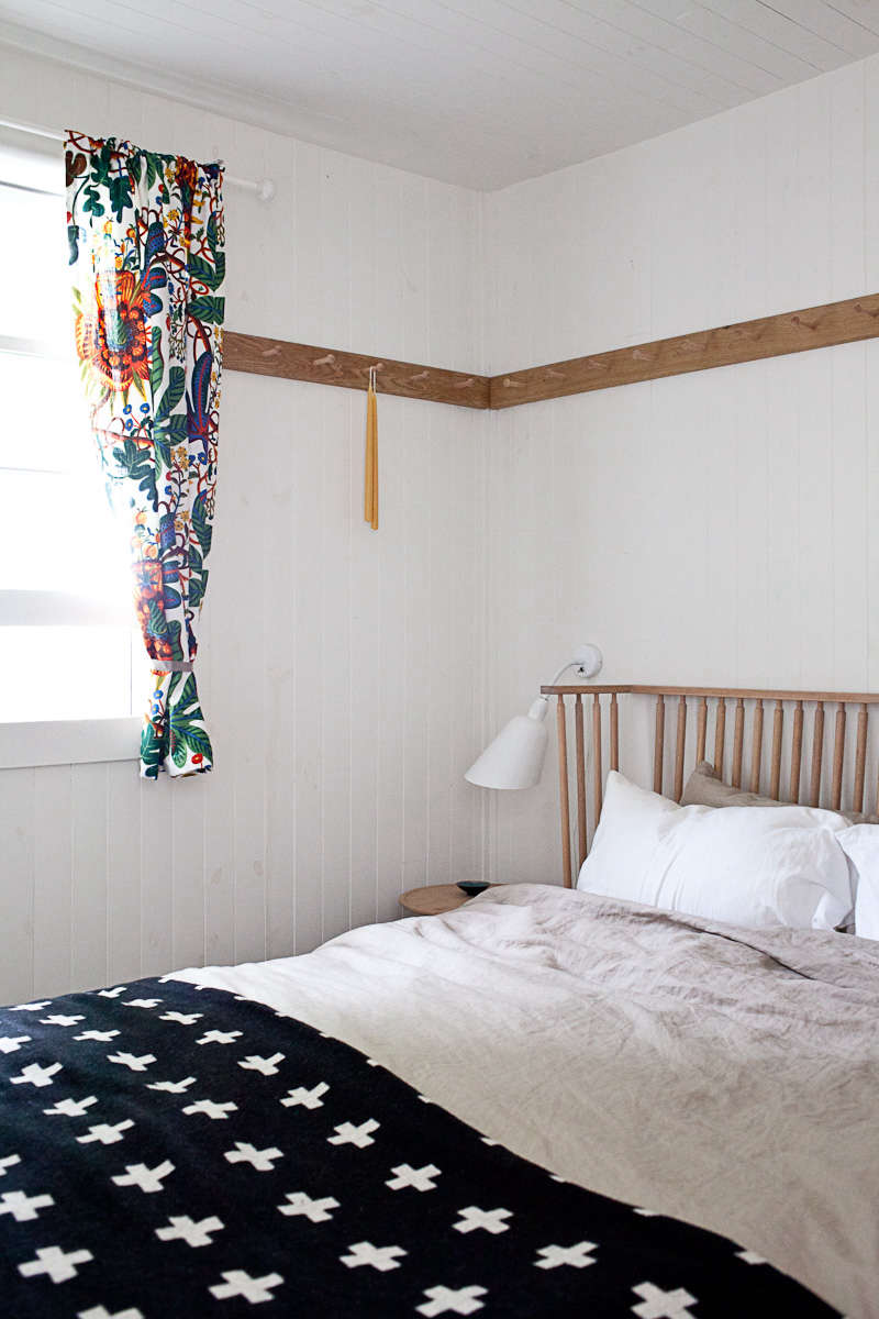An easy summer bedroom: peg rails in the Canadian summer cottage of Jon Baker and Juli Daoust of Mjolk. Photograph from O Canada: Mjölk's Renovated Scandi-Style Cabin on a Lake.