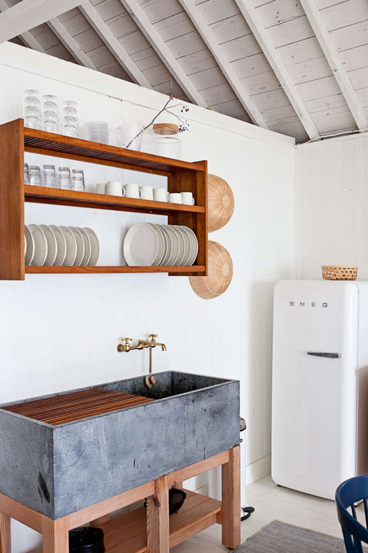 A custom wall-mounted dish rack hangs above a soapstone sink the cottage kitchen of John and Juli Baker of Mjölk.