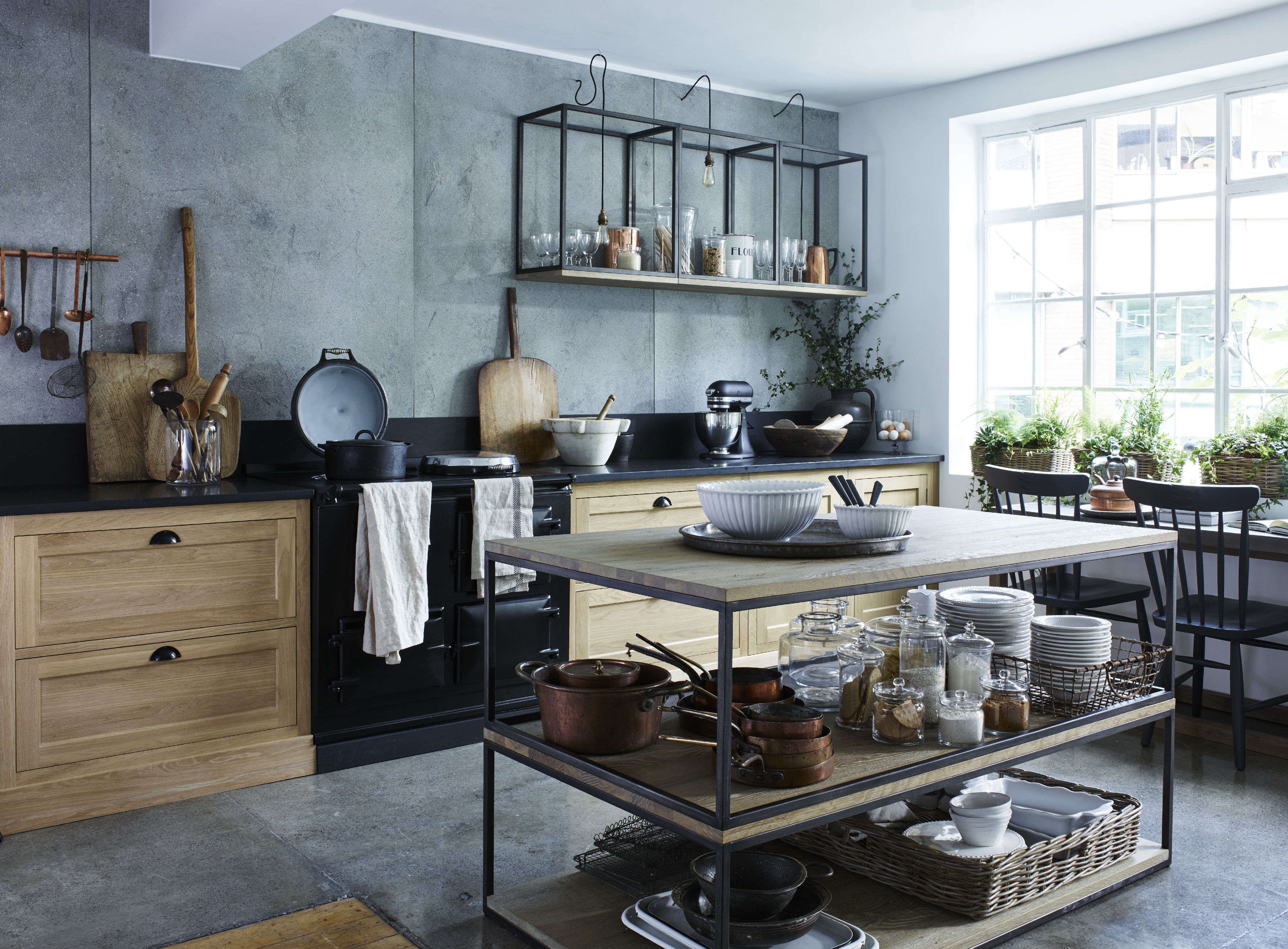 In the center of this kitchen, the stylists at the showroom have stacked two industrial-look coffee tables to create an open kitchen island and worktop. (Evidently, they've fashioned an extra surface at the base of the structure to create a third wooden shelf.)