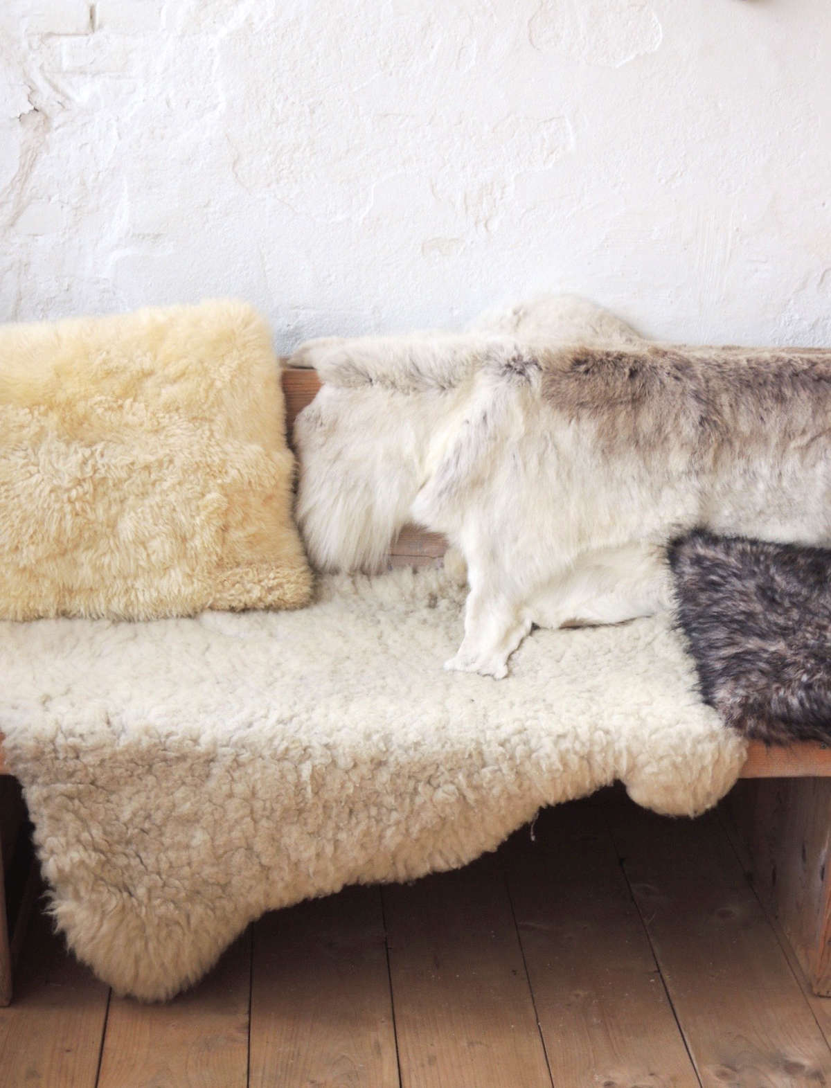 Sheepskins, hides, and pillows cover an unfinished wood bench.Photograph courtesy of Carla Zwart of Met Melk & Suikerfrom our post Through the Looking Glass:  New Trends for Fall .