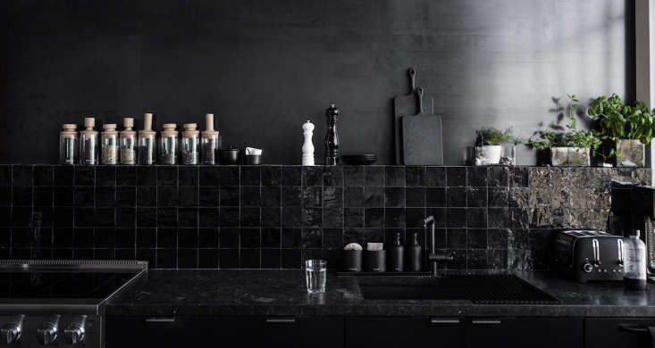An all-black kitchen—even the kitchen faucet is black—in the San Francisco studio of designer Nicole Hollis.