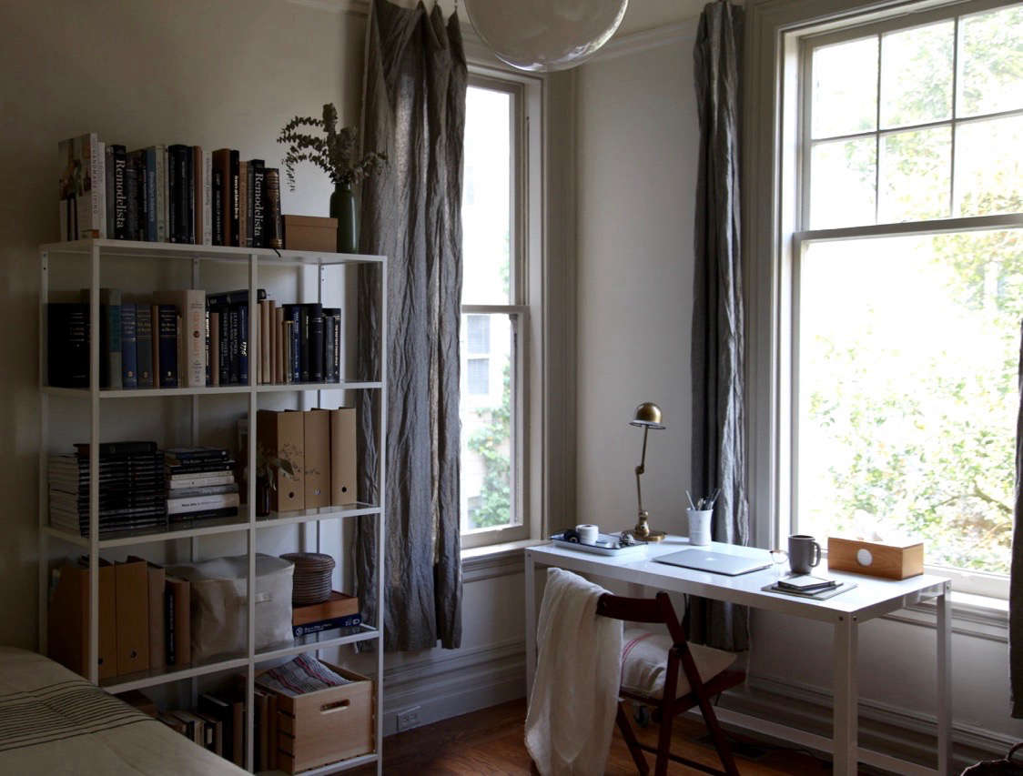 an apartment office with ikea bookshelf and diy linen curtains 17