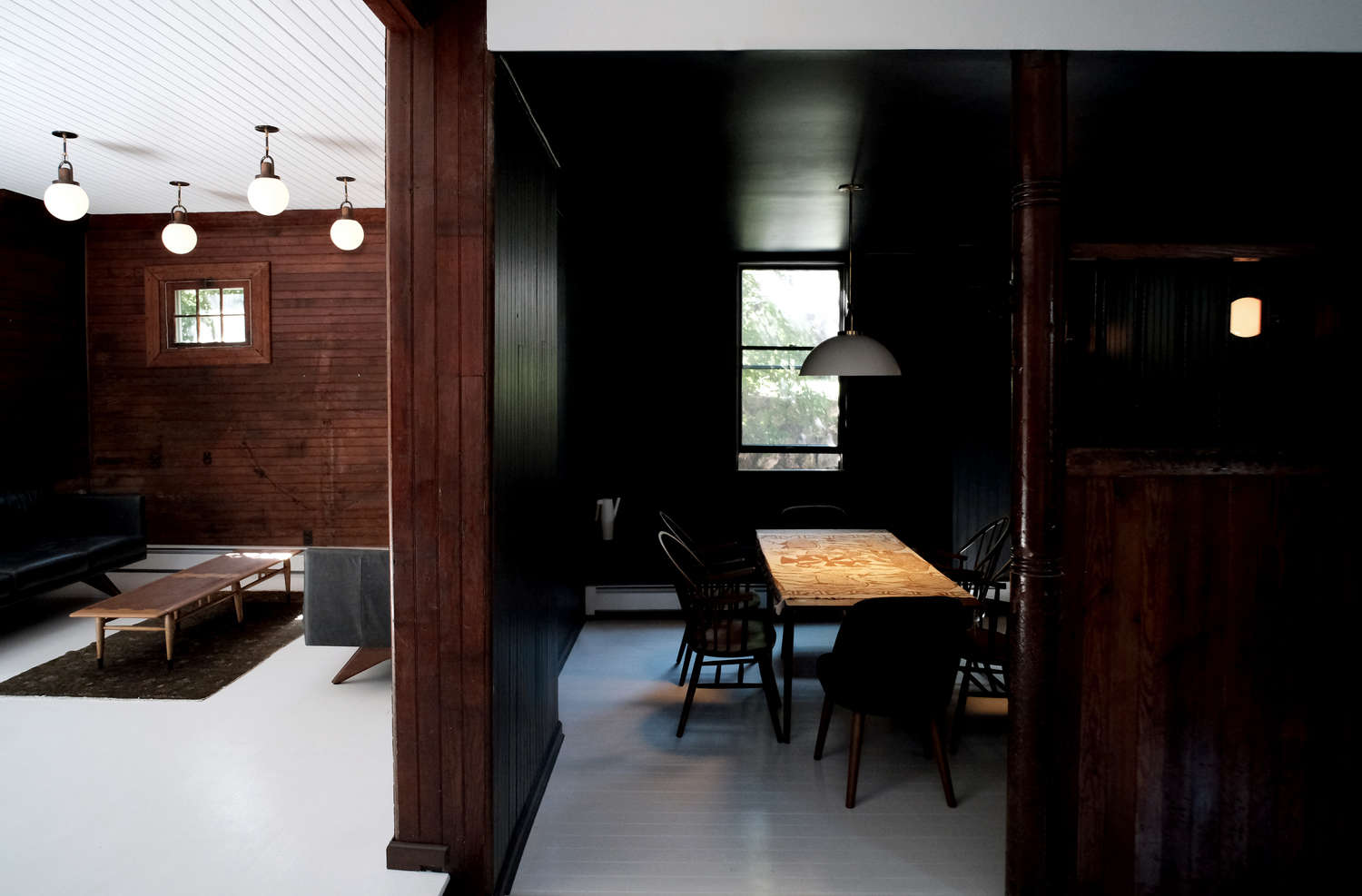 Before and After A Tuxedo Park Carriage House Gets an Update in Black and White Dark wood paneling on walls white floor space exploration