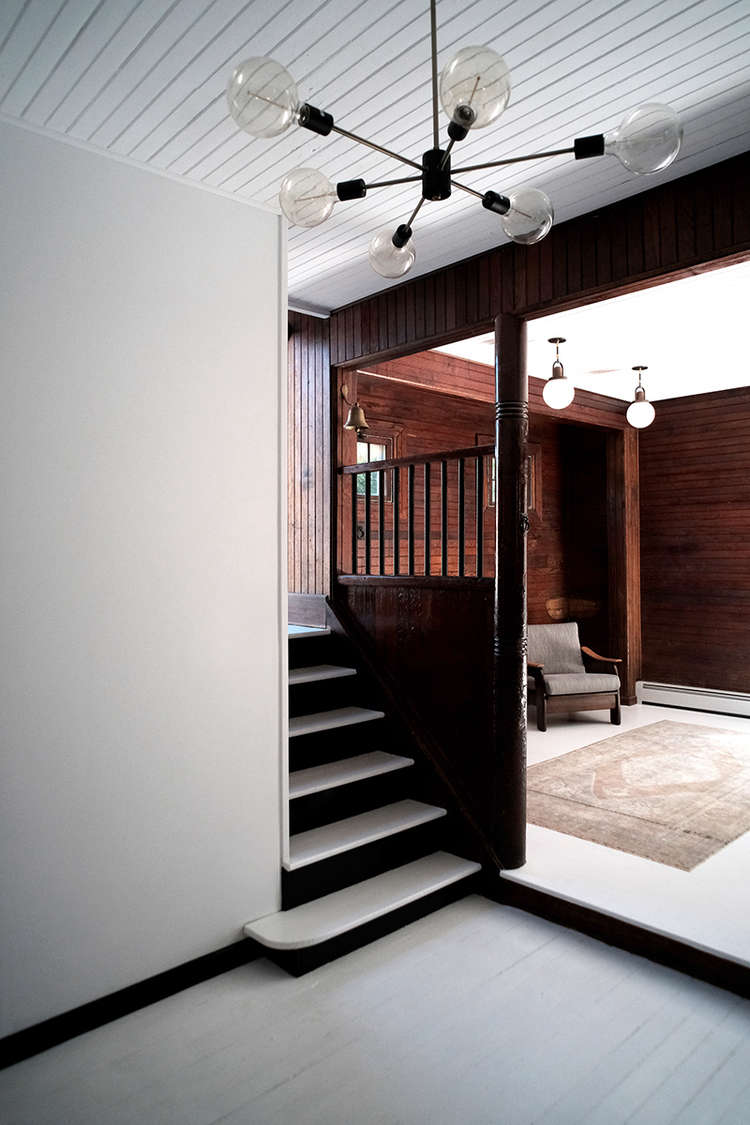 Before and After A Tuxedo Park Carriage House Gets an Update in Black and White Entry with stair and chandelier space exploration