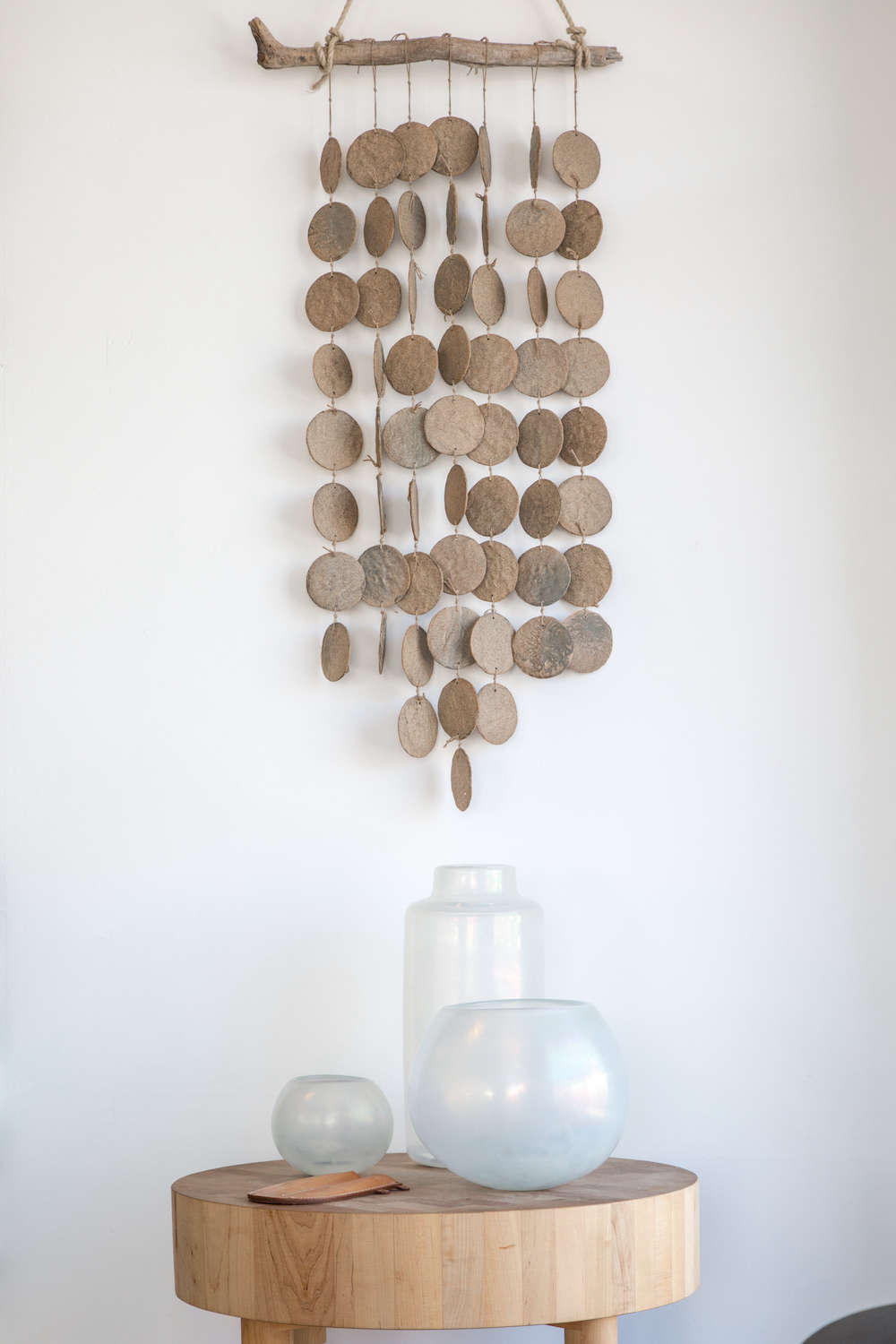 Ceramic mobile on white wall with hand-blown glass vases