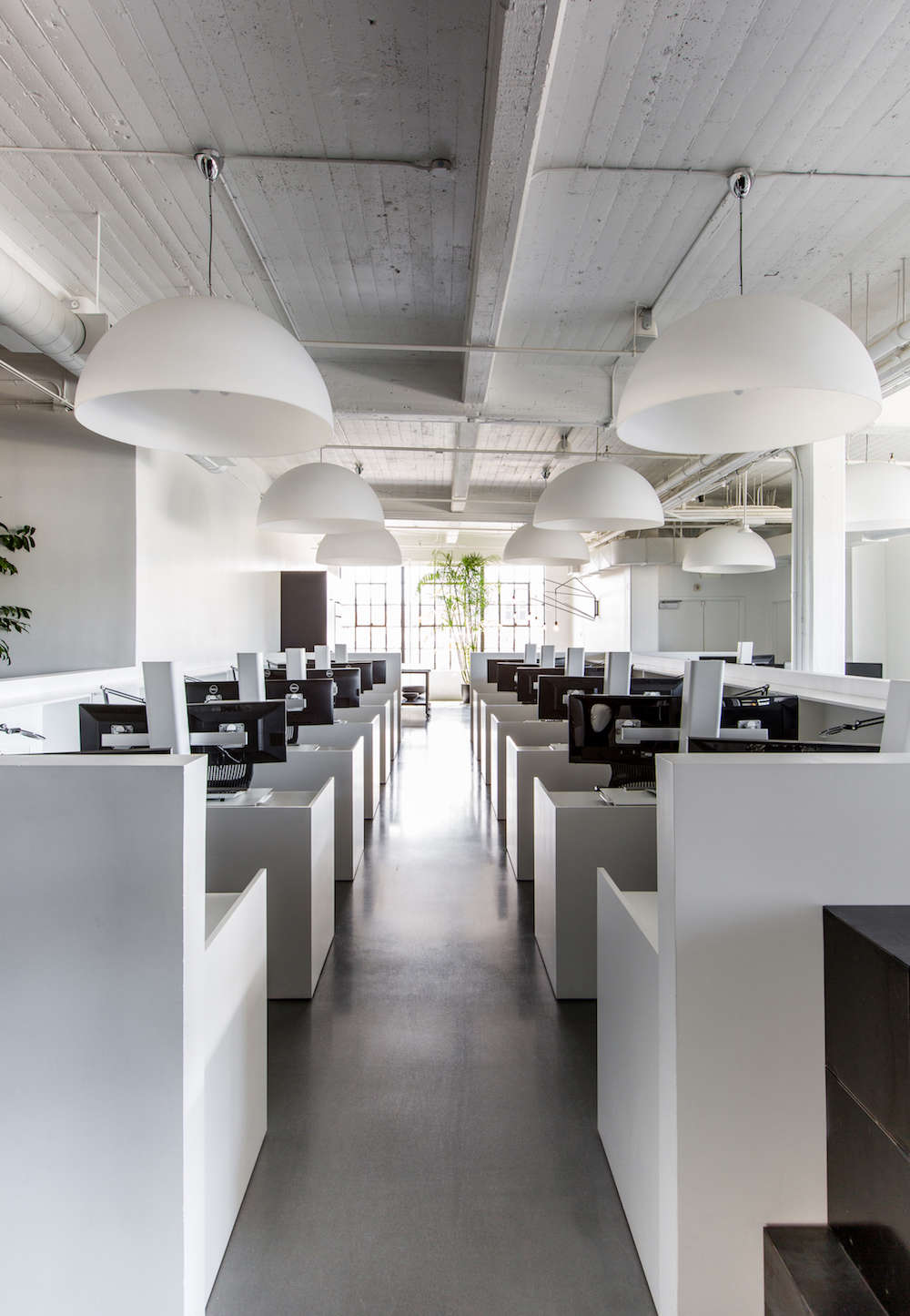 White Office Space with Dome Pendant Lights and Concrete Floors