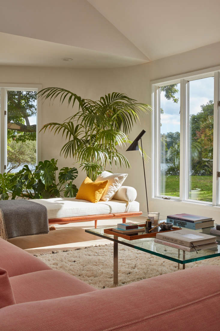 A pale tangerine pillow, pink sofa, and two green armchairs (not pictured here) anchor the living room. Photograph by Jonathan Hokklo.