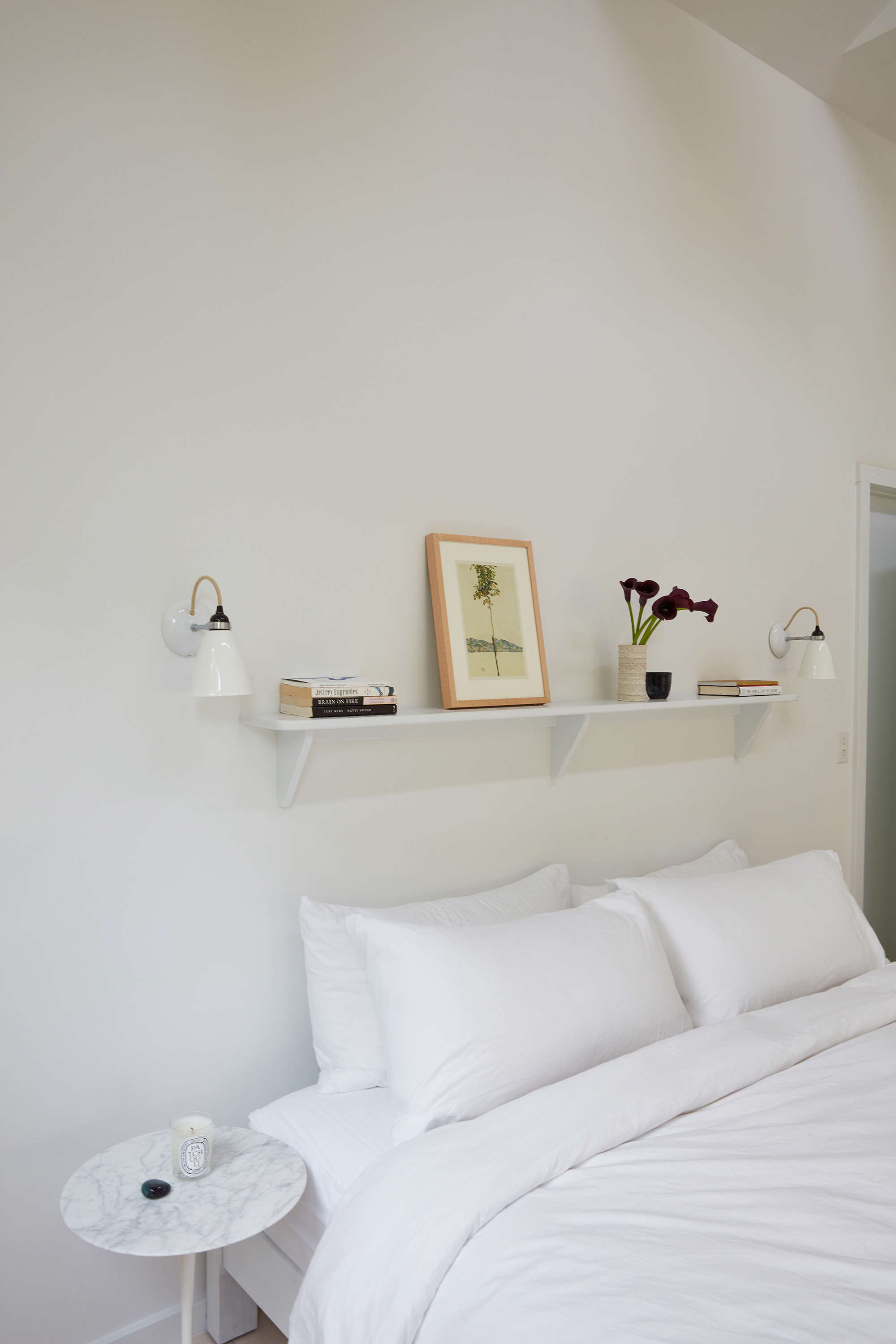 The original shelf above the bed got a fresh coat of white paintand are framed by a pair ofHector Wall SconcesfromDesign Within Reach.