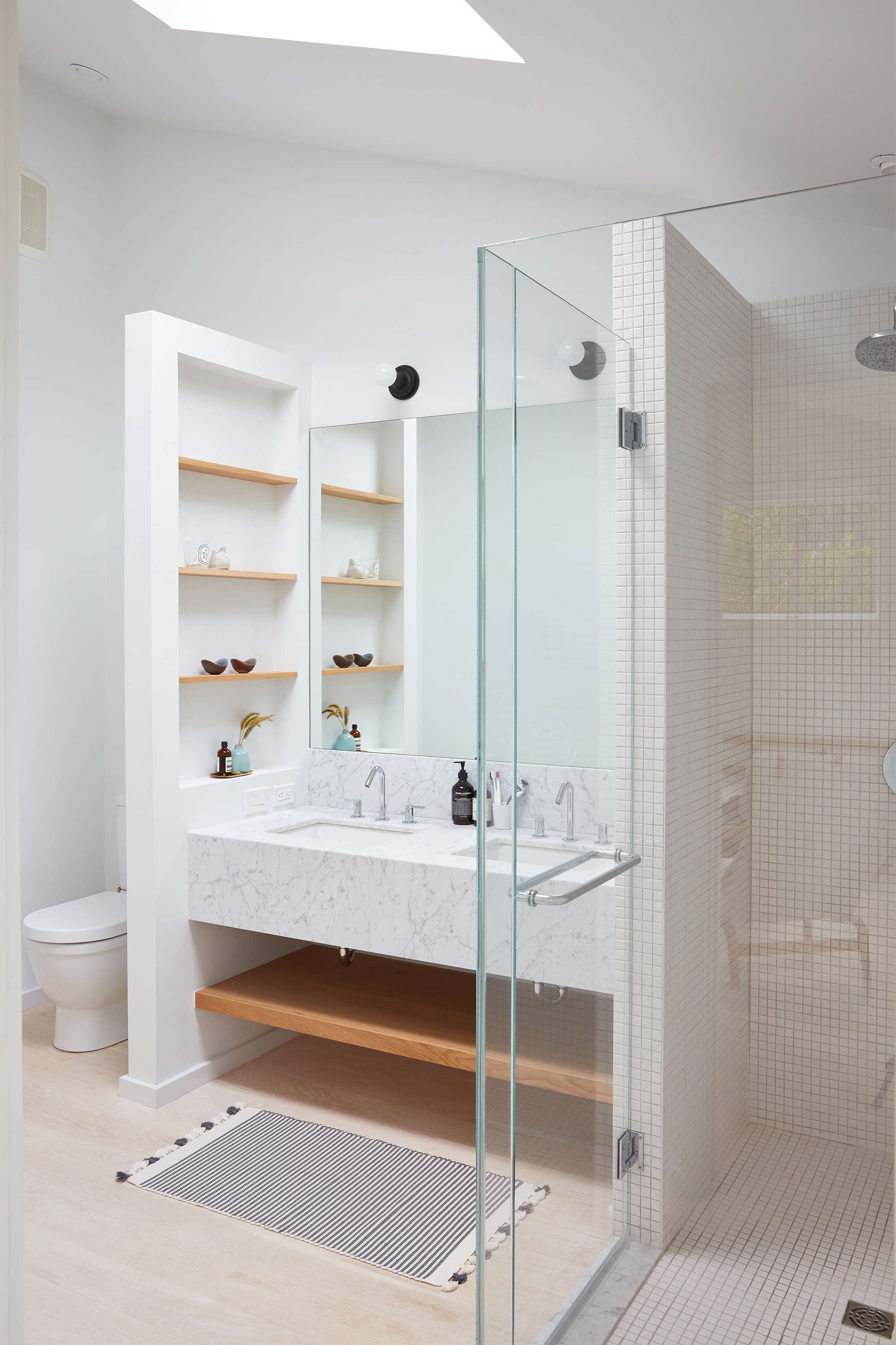 In the master bedroom, a custommarble vanity (also with marble fromABC Stone in Brooklyn) is fitted with custom oak shelves, perfect for storing bath essentials. A glass-enclosed shower usessquare tiles from Nemo Tile. The toilet is the Duravit Happy D., and the striped rug is from Nickey Keyhoe in LA.