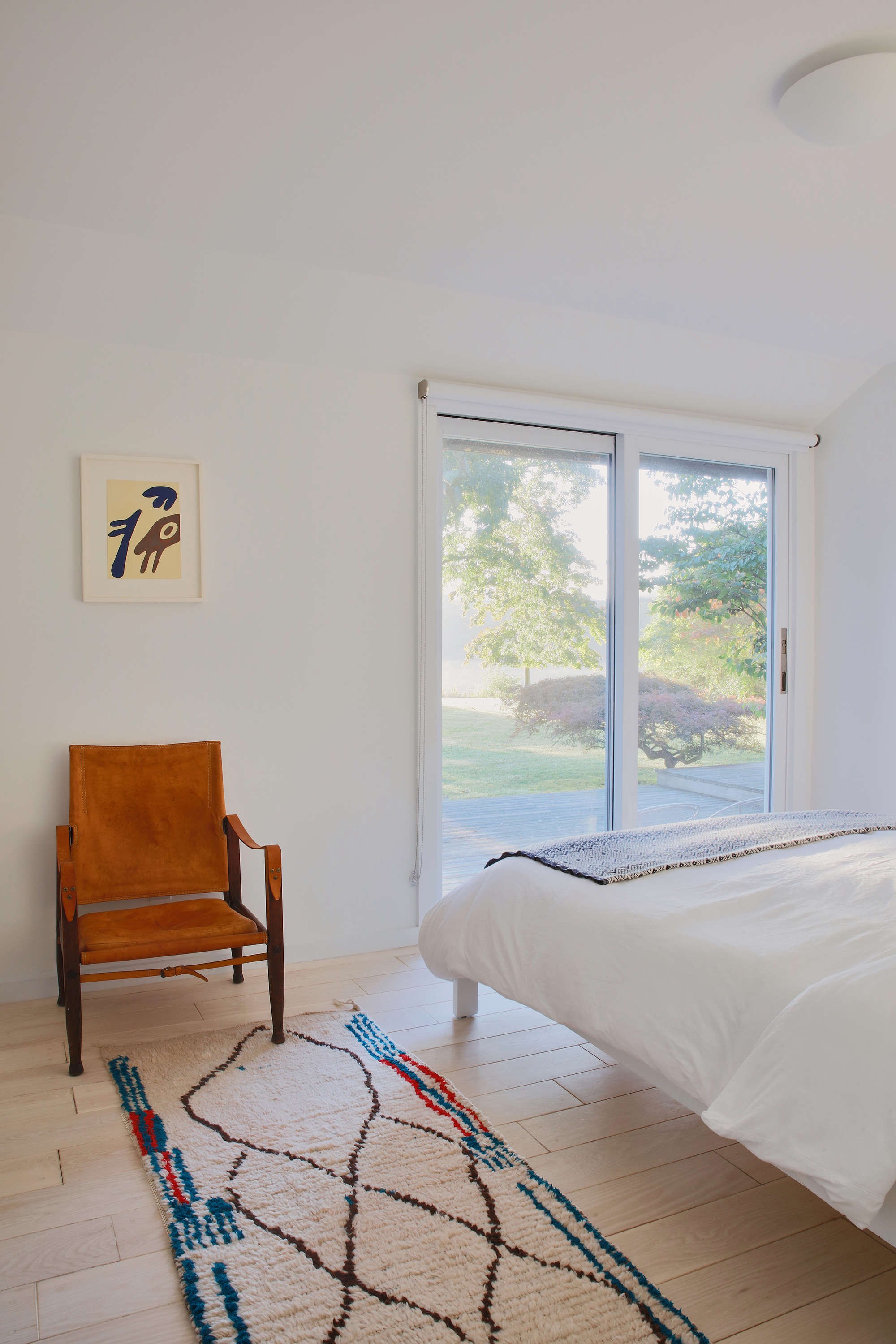 In another guest bedroom, a leather safari chair by Kaare Klintfrom Pamonoanda Moroccan rug fromLarusi in London (&#8