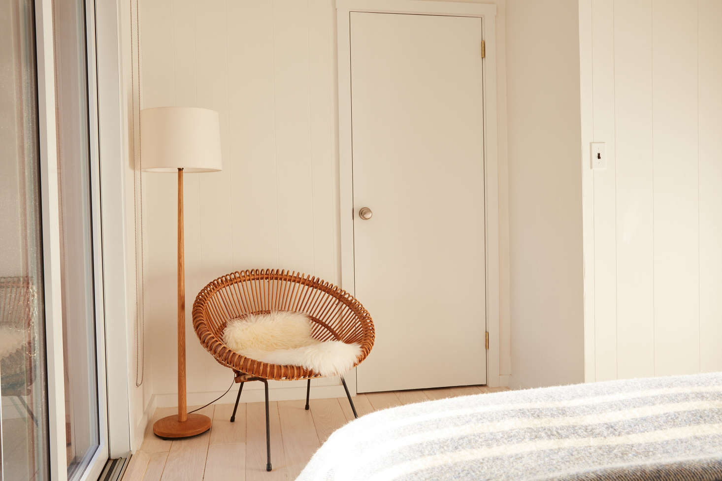 At the foot of the bed: a rattan Franco Albini chair, a Danish standing lamp from Etsy, and the door to an en suite bedroom.