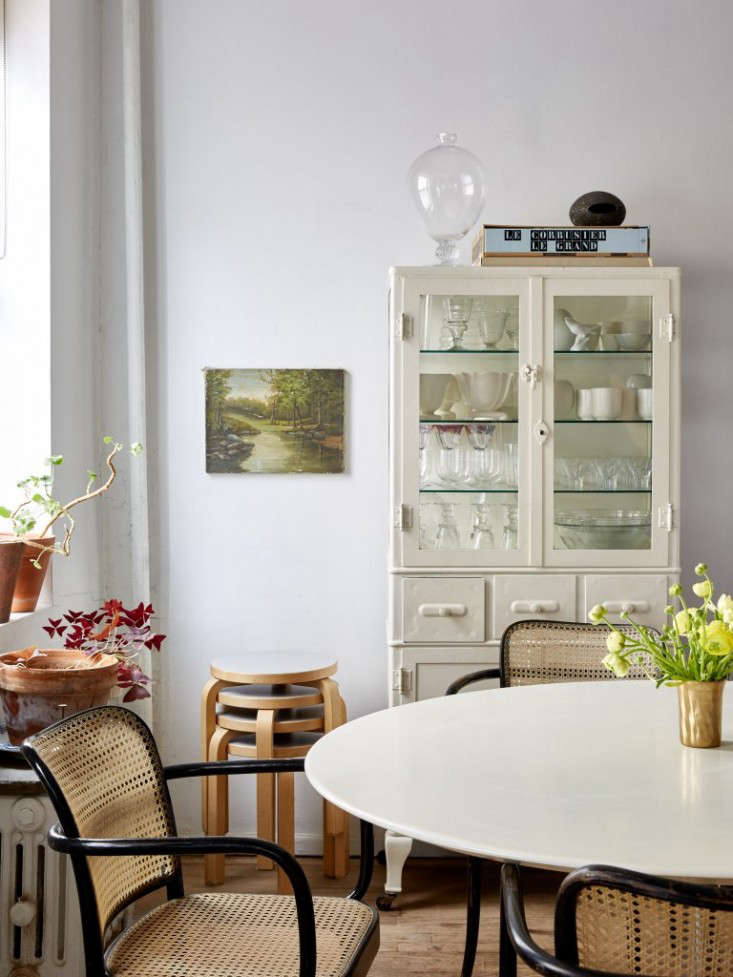 Efficient vertical storage, including stacking stools and a tall hutch, as seen in Small-Space Solutions:  Affordable Tips from an NYC Creative Couple.