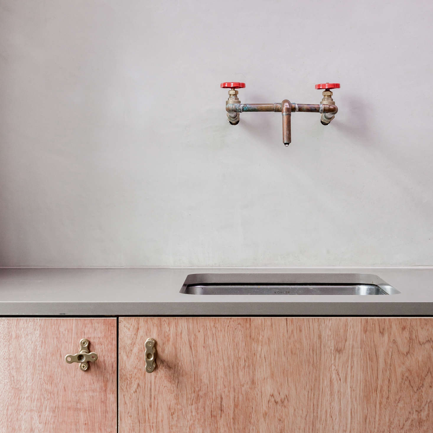 Brass kitchen faucet made from plumber's parts in a kitchen designed by architect Simon Astridge