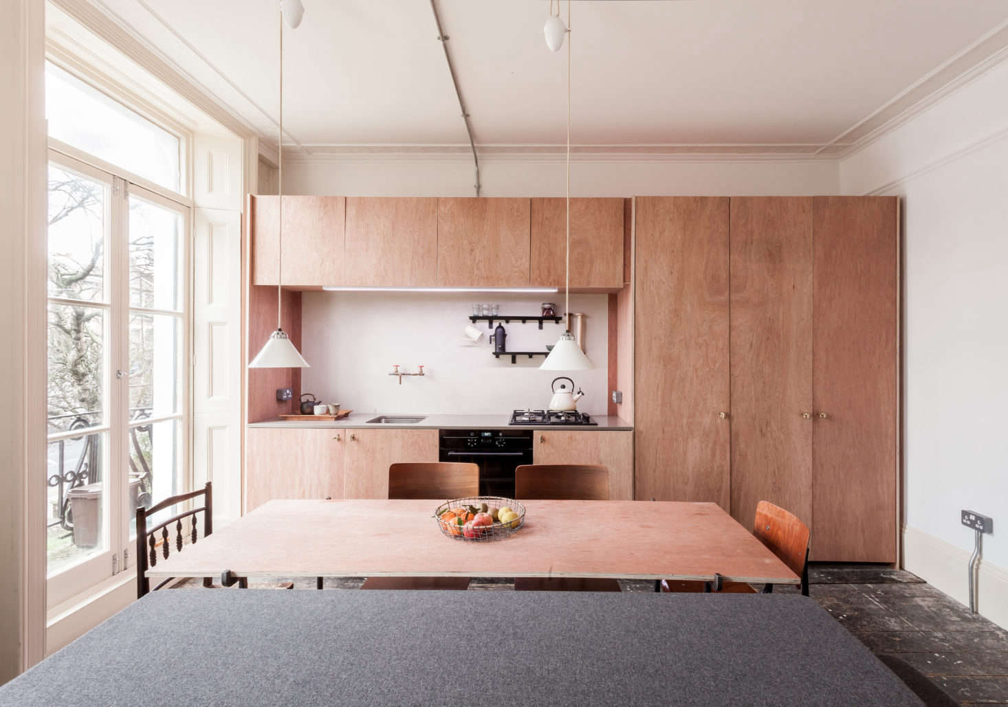Plywood cabinets in a small kitchen open to dining and living area, designed by London architect Simon Astridge