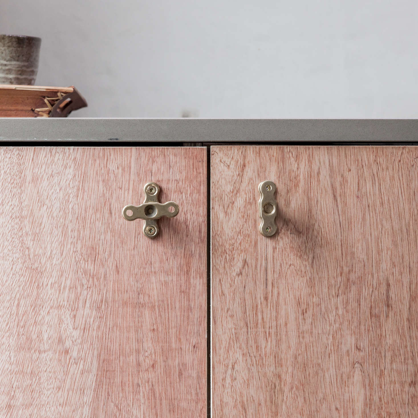 Plywood cabinets with cabinet knobs made from brass plumbing parts, designed by London architect Simon Astridge