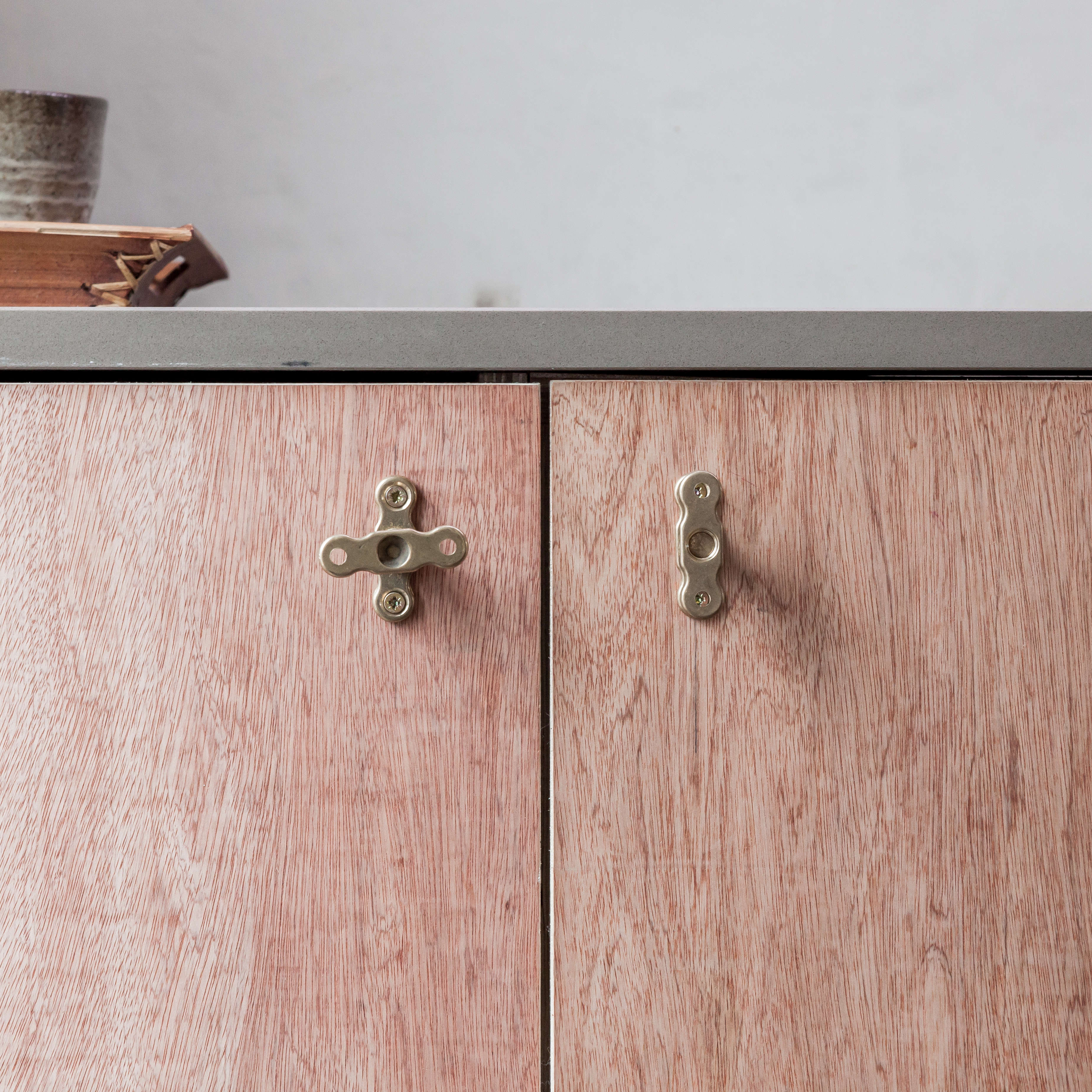 plywood cabinets with cabinet knobs made from brass plumbing parts, designed by 15
