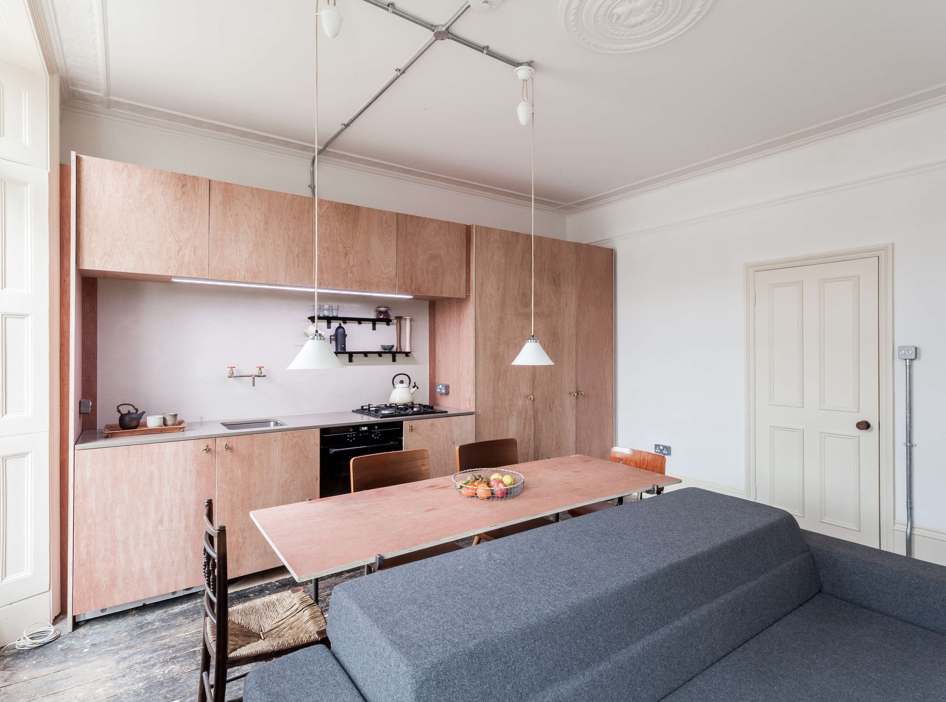 plywood cabinets in a small kitchen open to dining and living area, designed by 12