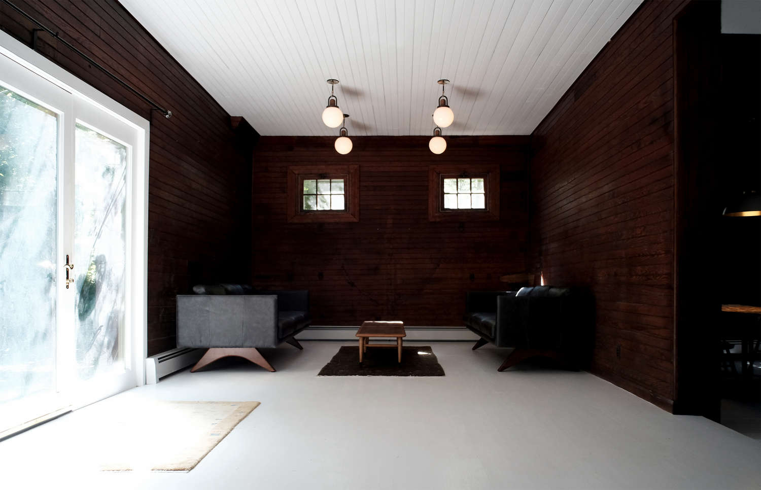 Before and After A Tuxedo Park Carriage House Gets an Update in Black and White dark paneled living room white ceiling space exploration