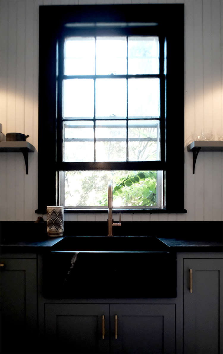 Before and After A Tuxedo Park Carriage House Gets an Update in Black and White kitchen sink black with black windows space exploration