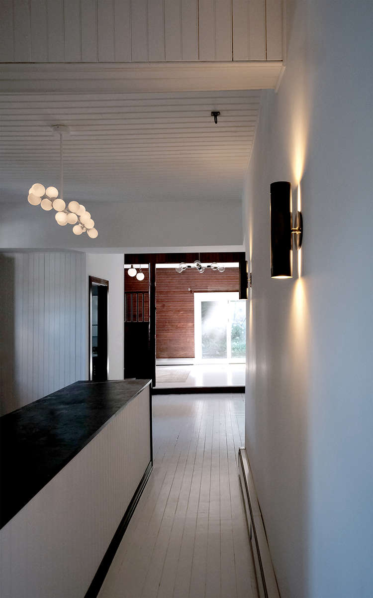 Before and After A Tuxedo Park Carriage House Gets an Update in Black and White white painted walls and floors carriage house space exploration