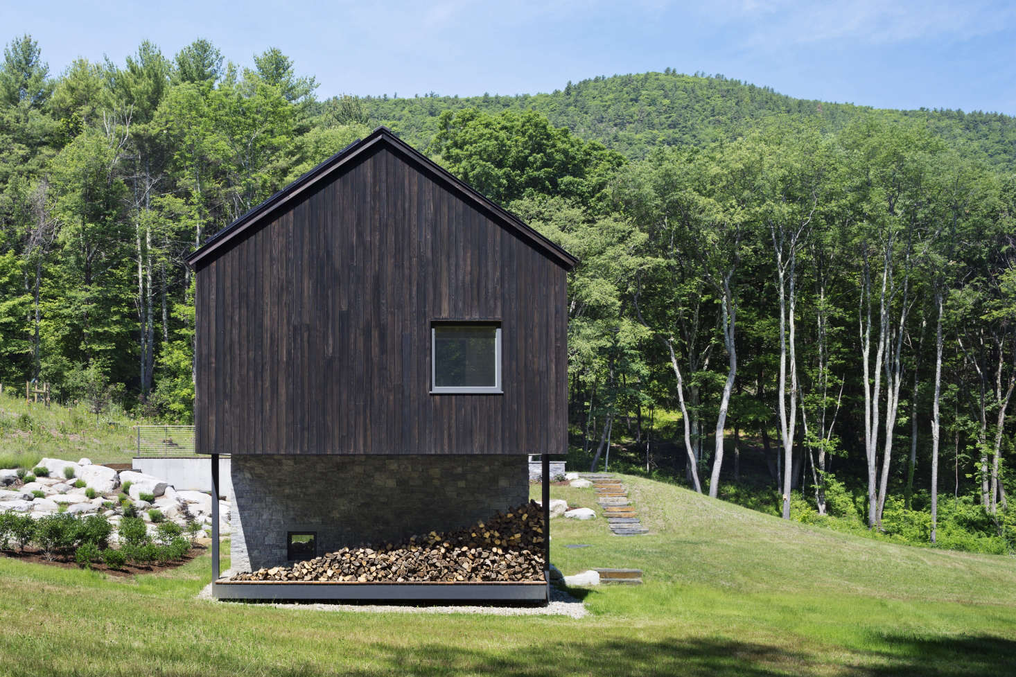 A wood pile screens off an outdoor shower under the cantilevered end of Undermountain, a barn-style house in the Berkshires by O'Neill Rose Architects