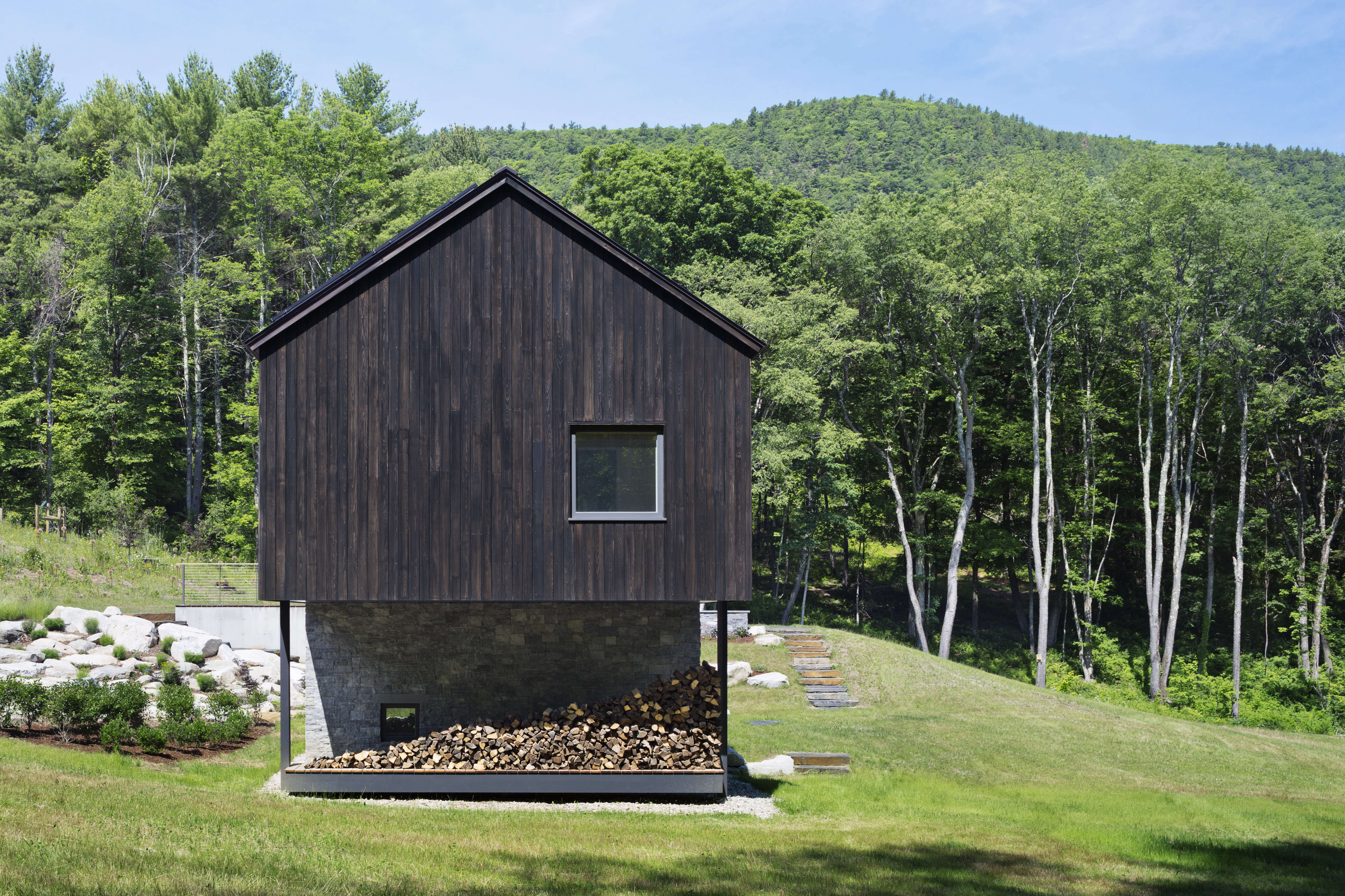 a wood pile screens off an outdoor shower under the cantilevered end of undermo 22