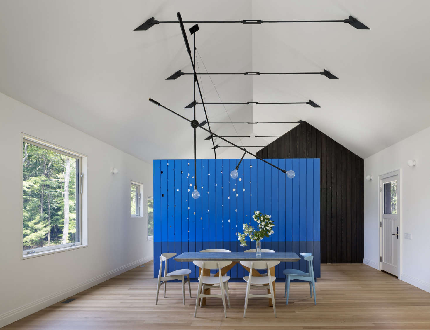 A screen as a room divider at Undermountain, a barn-style house in the Berkshires by O'Neill Rose Architects